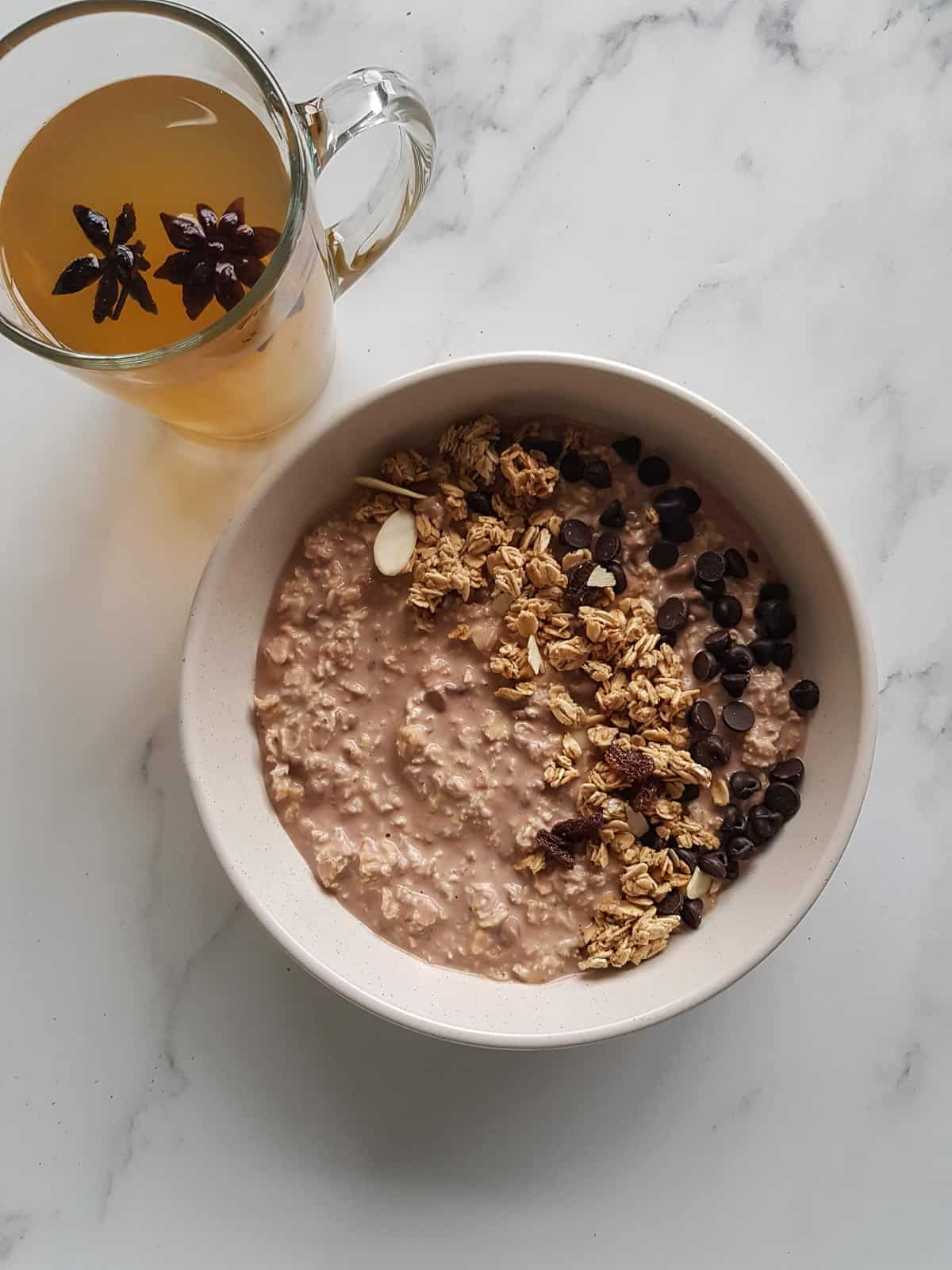 A bowl of chocolate overnight oats, with a cup of tea on the side.