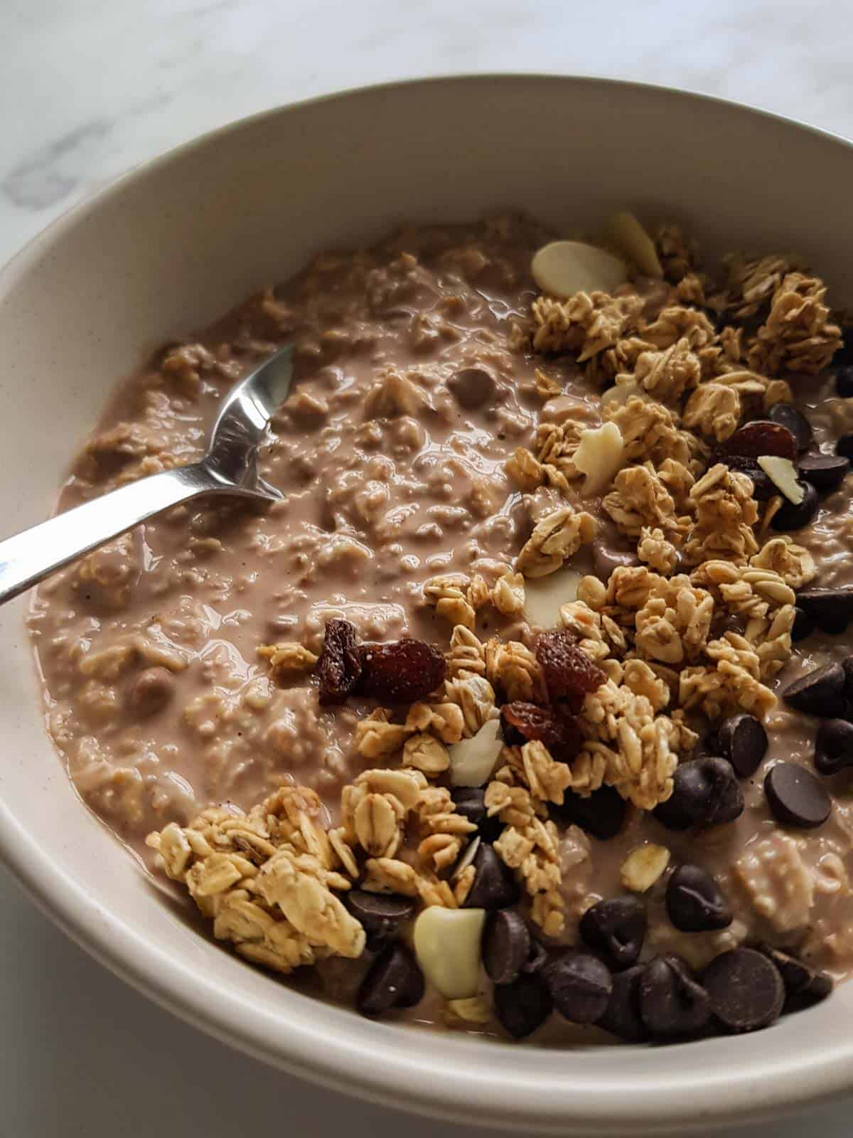 Close up of chocolate overnight oats in a bowl with granola and chocolate chips on top.