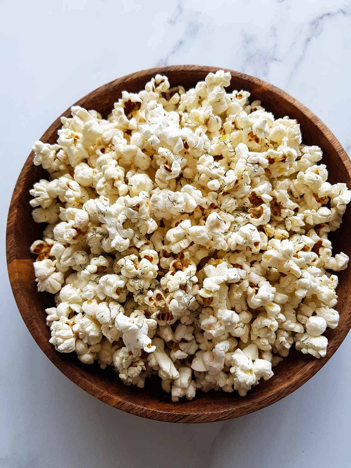 Dill pickle popcorn in a wooden bowl.