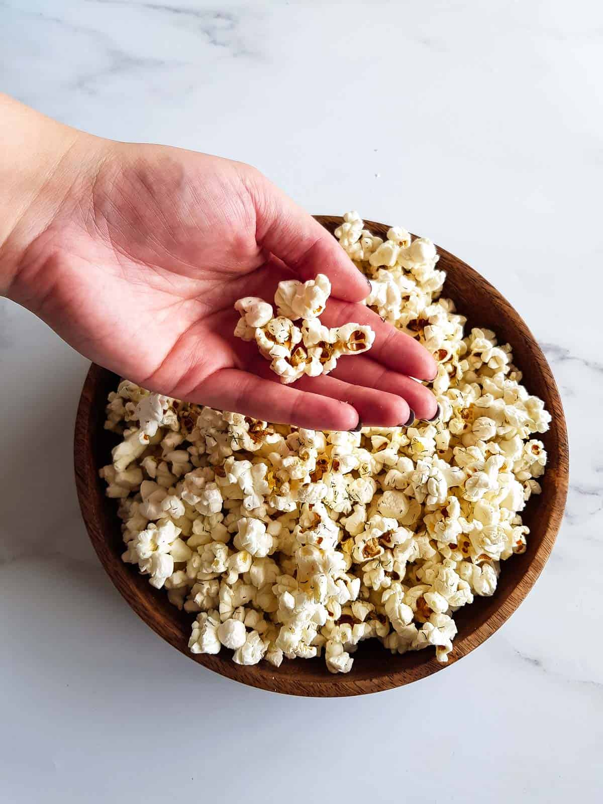 A hand grabbing a portion of popcorn from a wooden bowl.