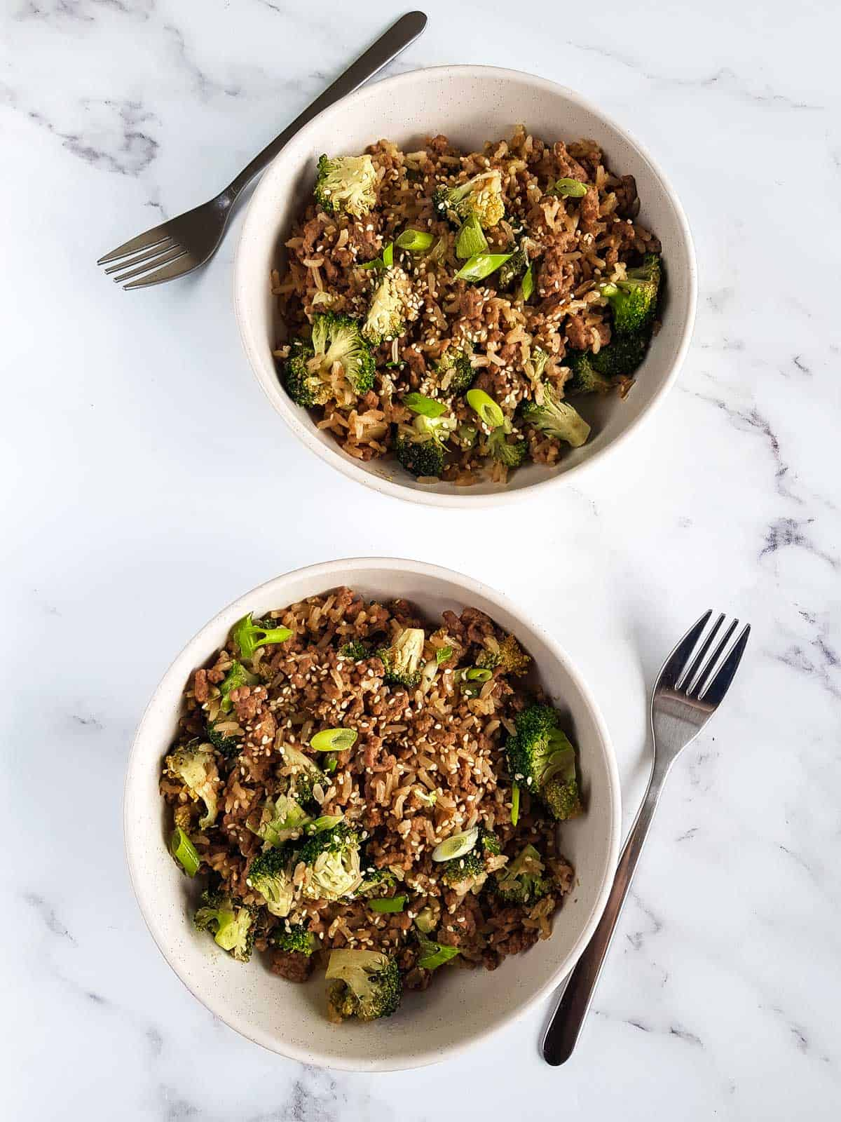 Two bowls of ground beef and broccoli on a table, with forks next to them.
