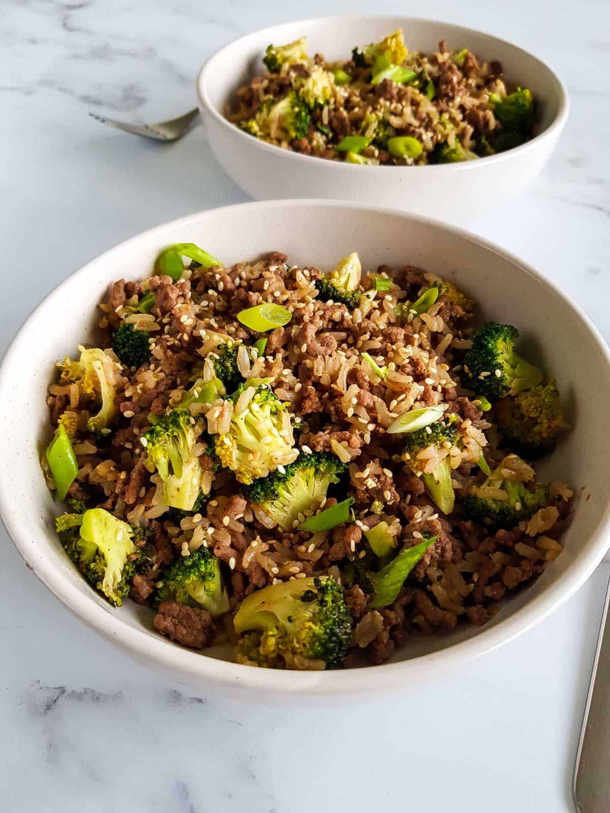 A bowl of broccoli, rice and ground beef with a fork next to it.