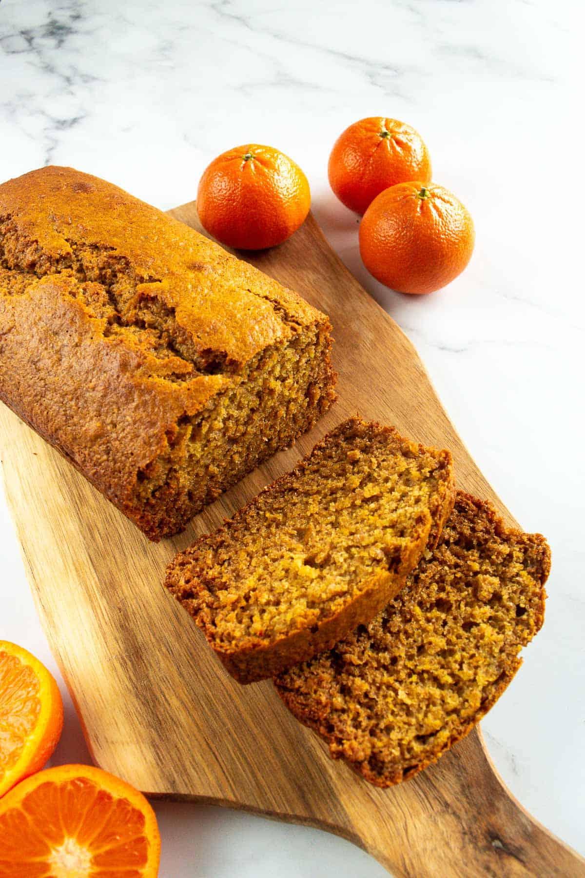 Sliced orange loaf with oranges on the side.
