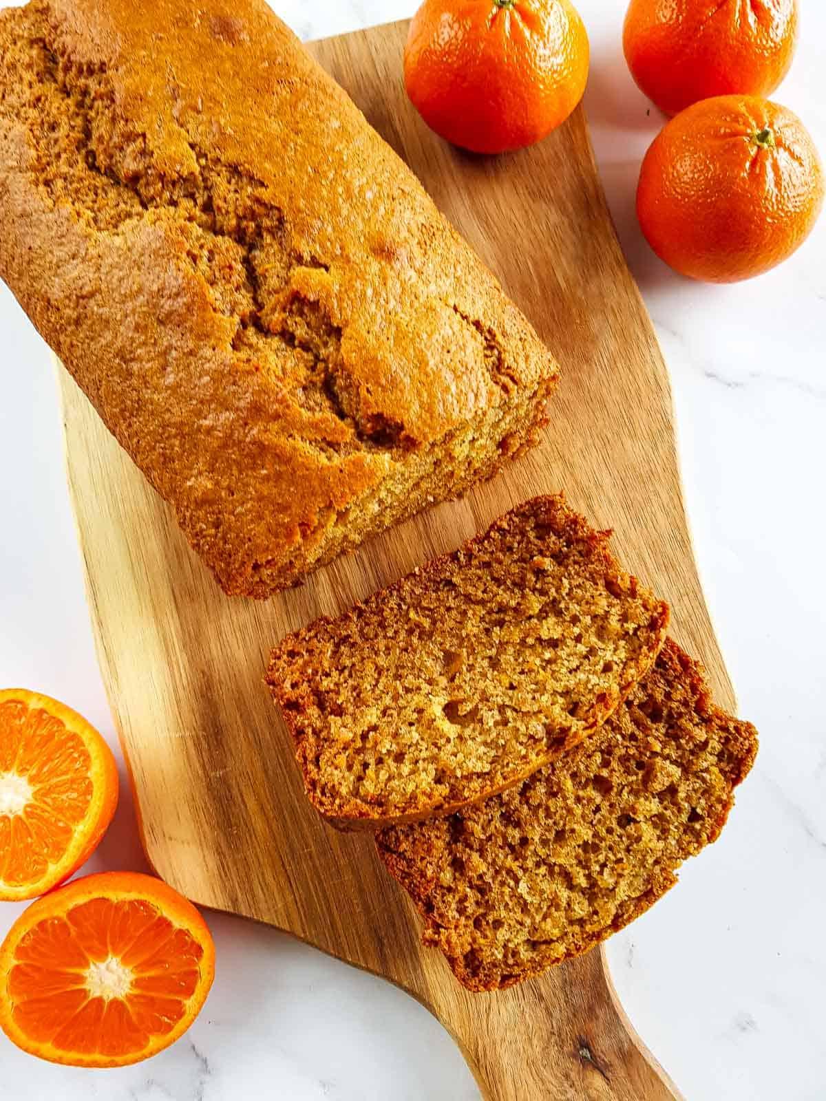 Orange loaf cake on a wooden board.