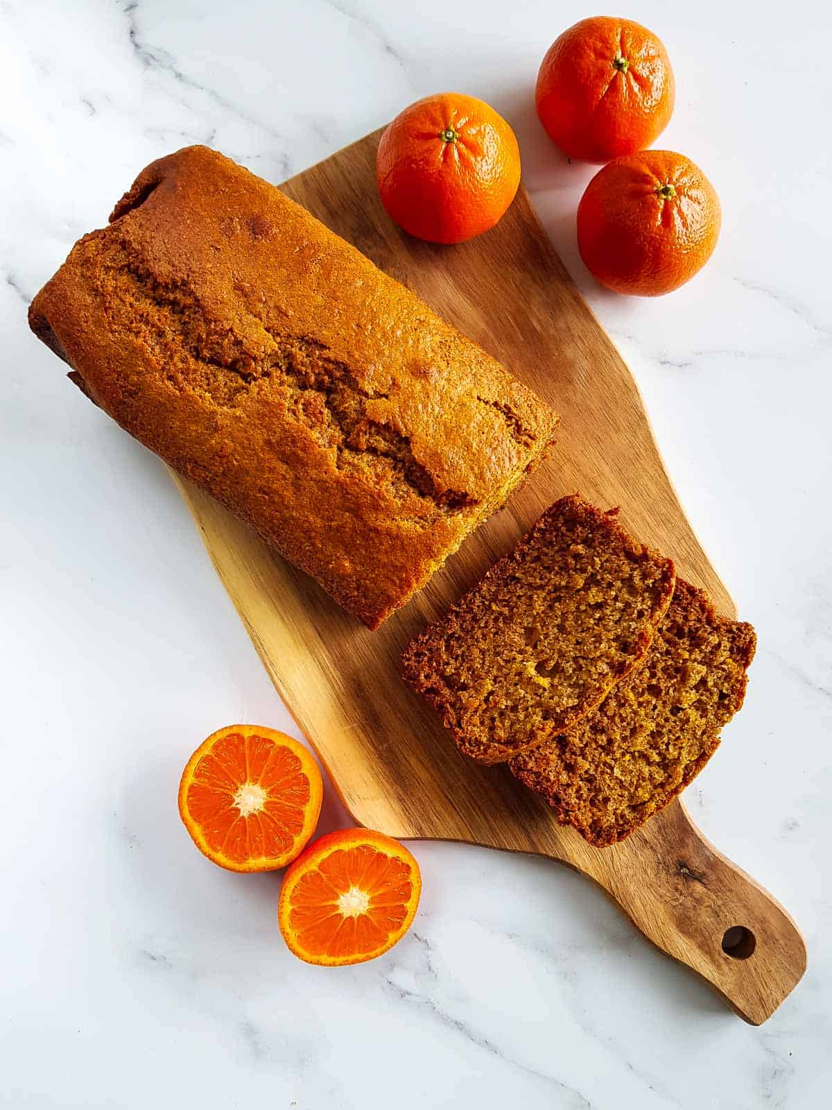 Healthy orange loaf cake on a wooden chopping board, with two slices sliced off.