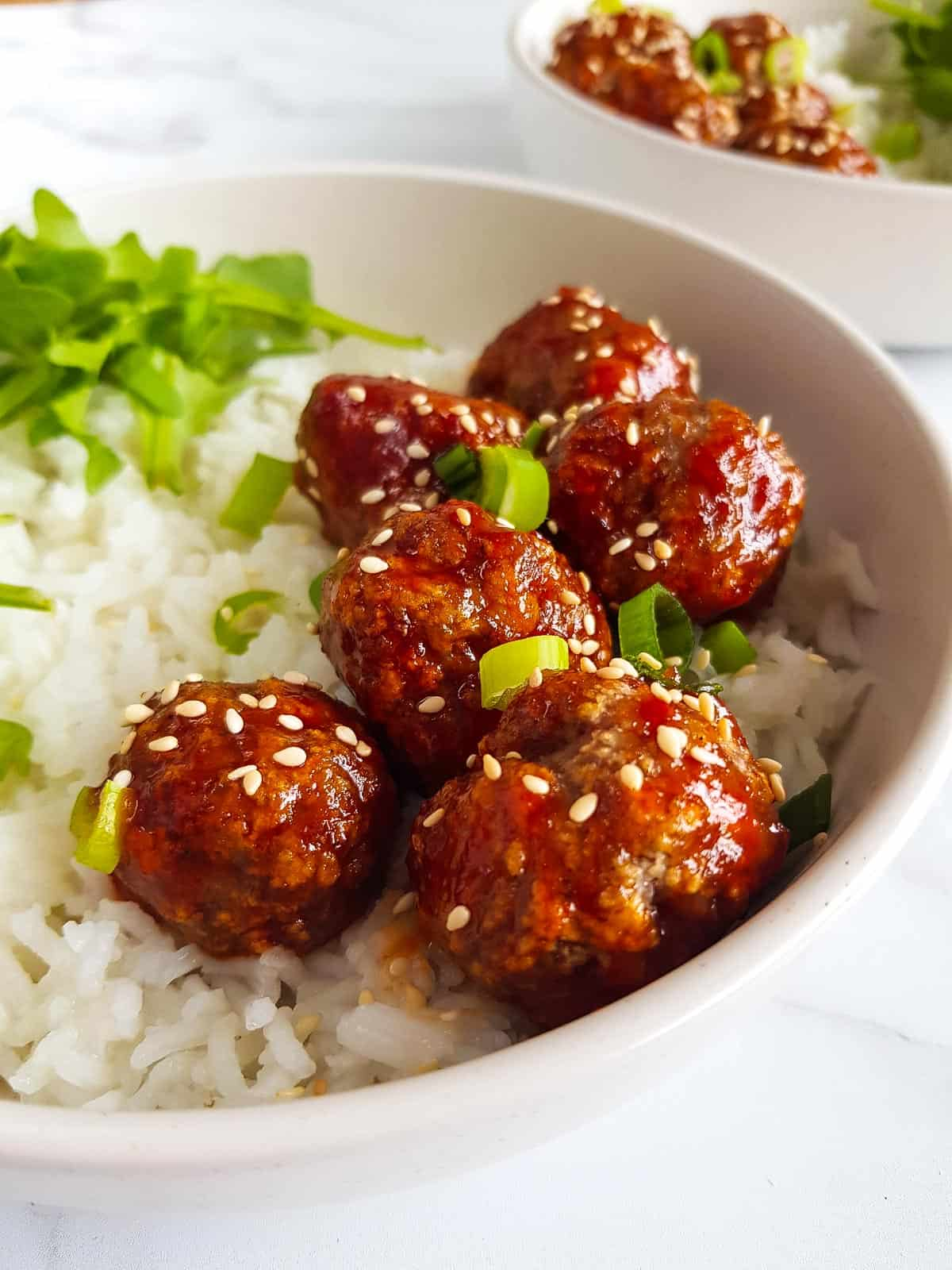 A bowl of honey sriracha meatballs and rice.