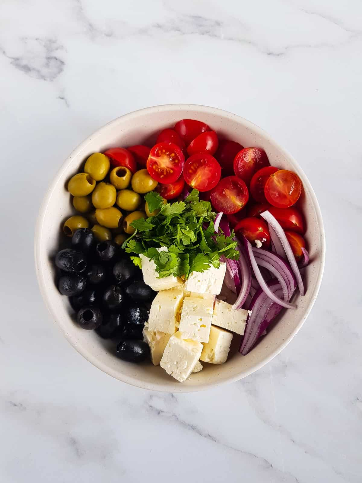 Black and green olives, tomatoes, feta, herbs and red onion in a bowl.