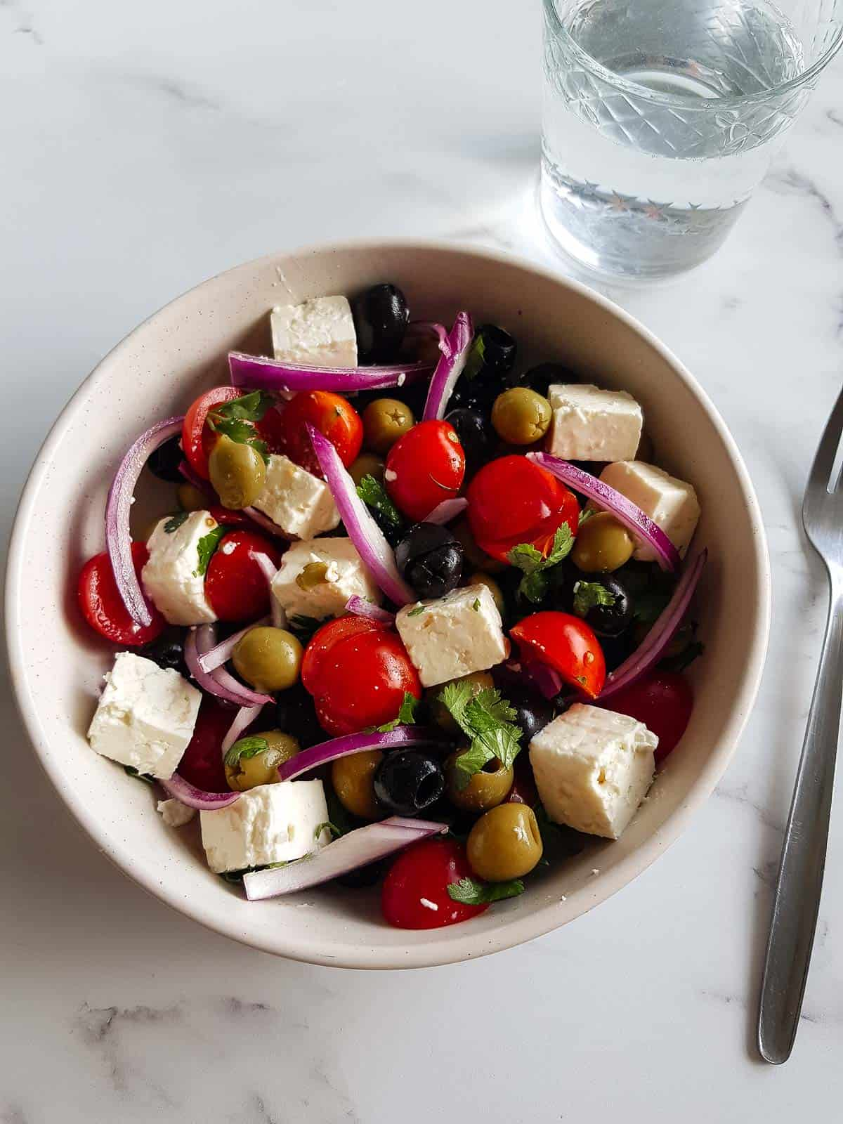 Olive salad in a bowl with a glass of water and a fork on the side.