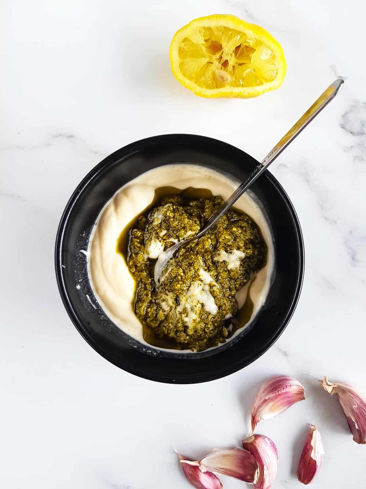 Mixing pesto and mayonnaise in a bowl, with garlic cloves and half a lemon on the side.