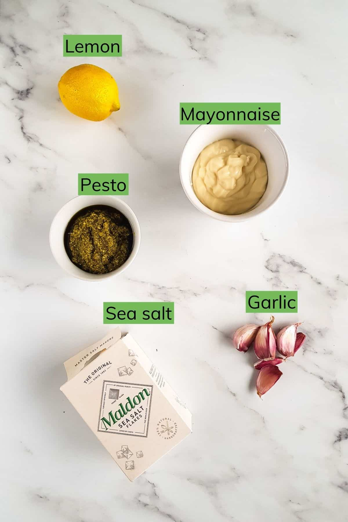 Garlic, lemon, mayonnaise, pesto and salt sitting on a table.