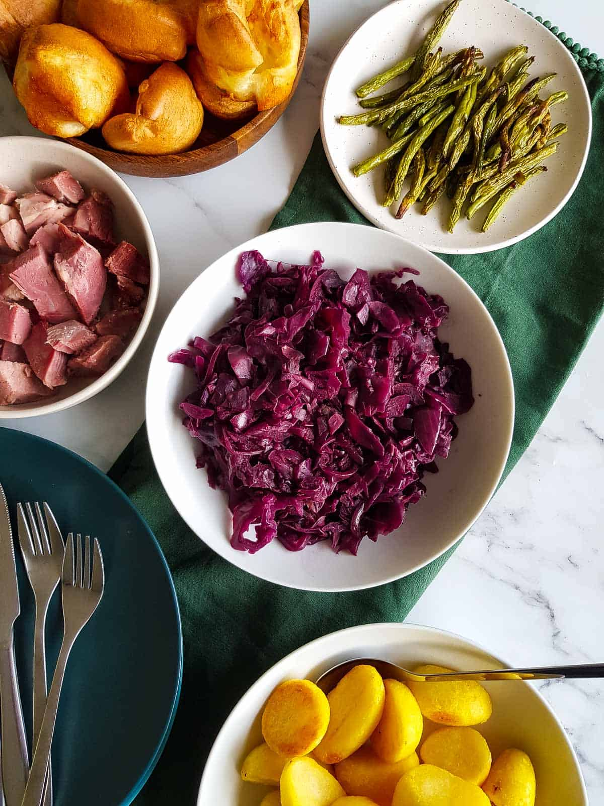 A roast dinner table with several side dishes, including red cabbage.