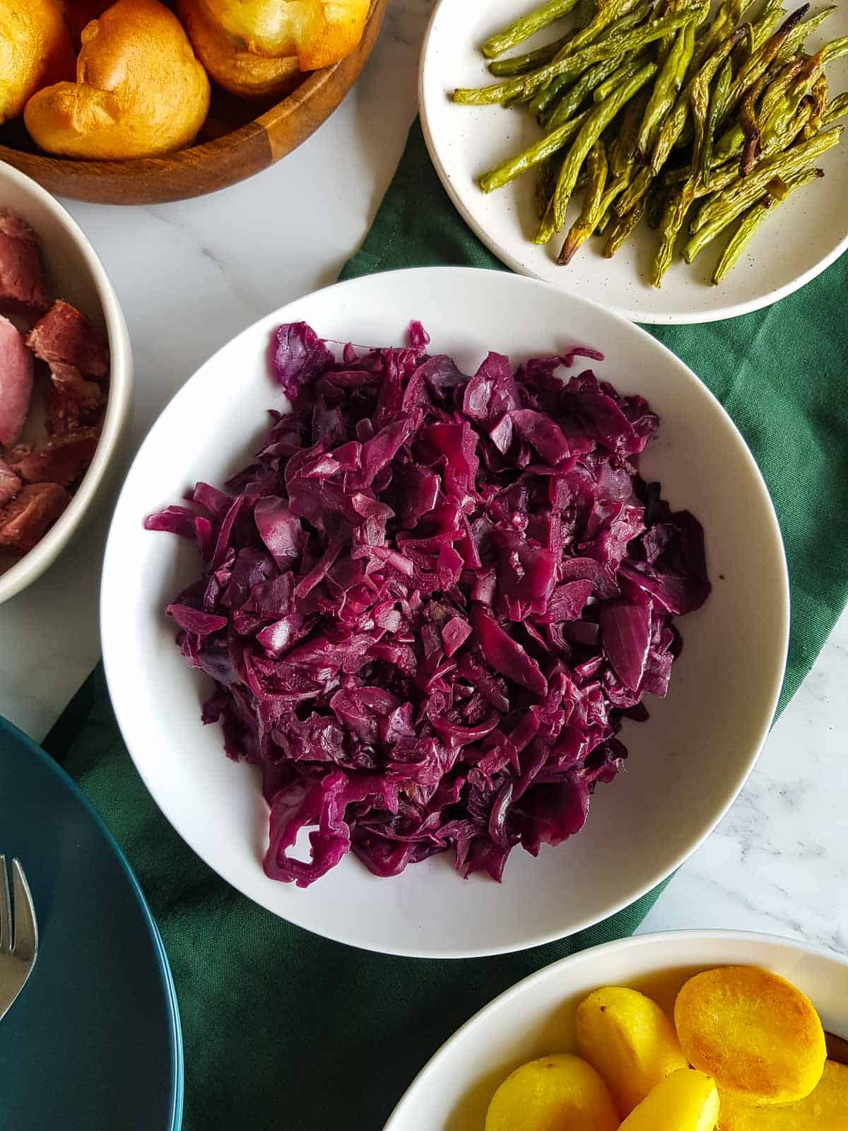 A bowl of slow cooker red cabbage on a table, surrounded by other dishes.