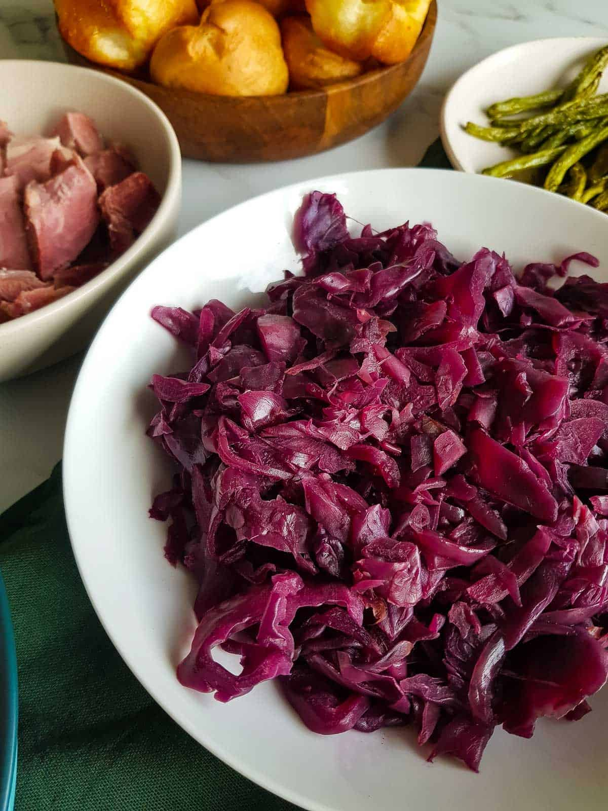 Close up of red cabbage in a bowl at a dinner table.