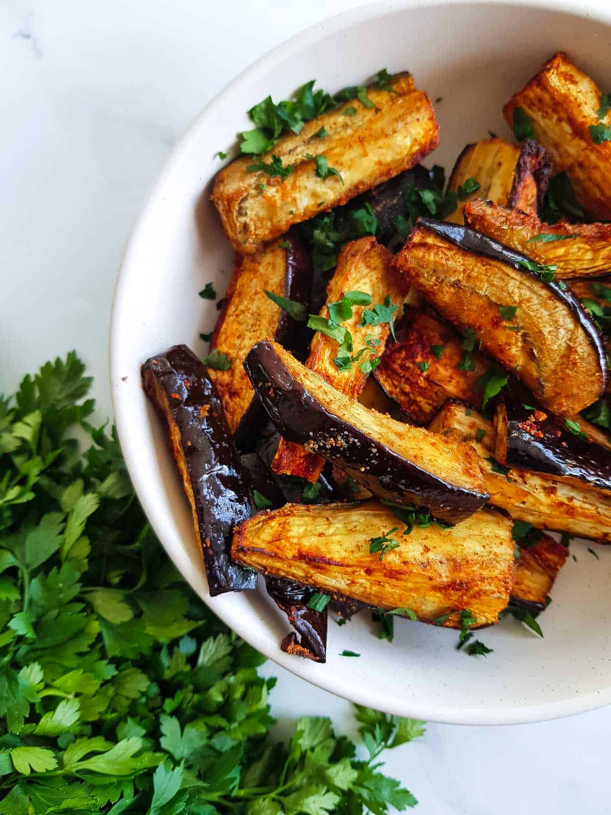 A white bowl of air fryer eggplant with parsley on the side.