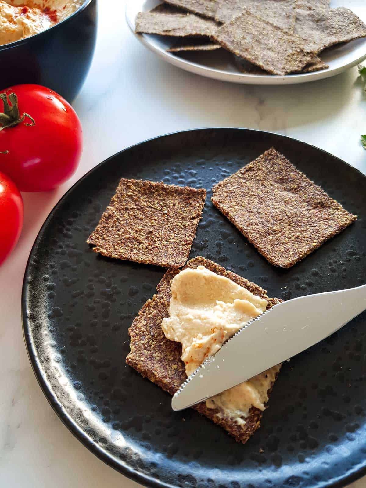 A knife spreading hummus onto a flax seed cracker.