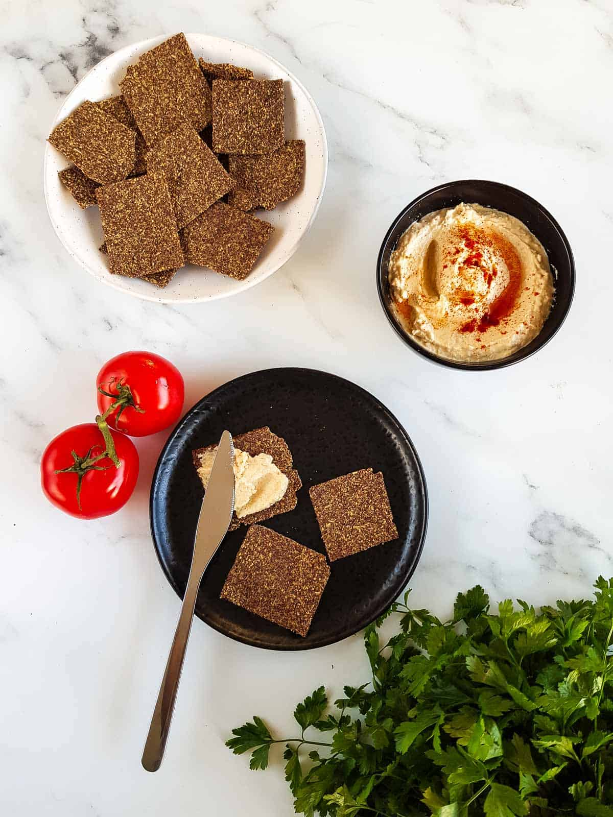 Flaxseed crackers on a plate, with a knife spreading hummus on top. A bowl of hummus and tomatoes on the side.