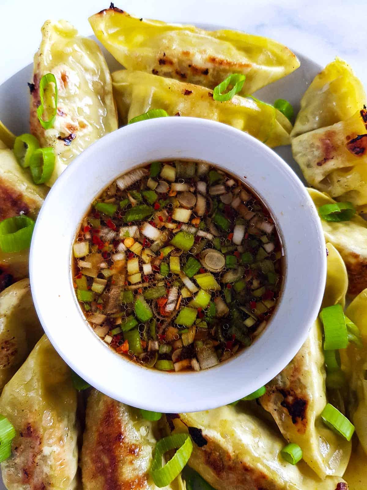 Gyoza sauce on a plate surrounded by gyozas.