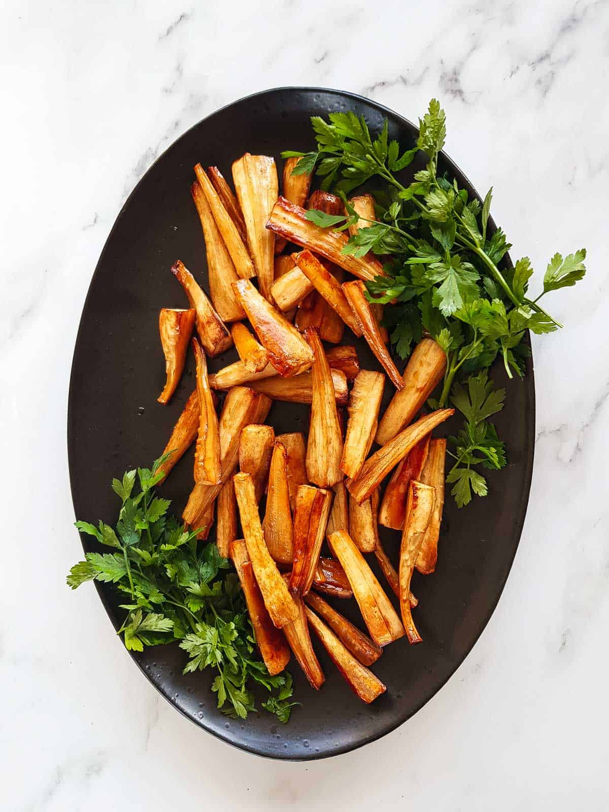 Honey roast parsnips on a serving platter with fresh parsley garnish.