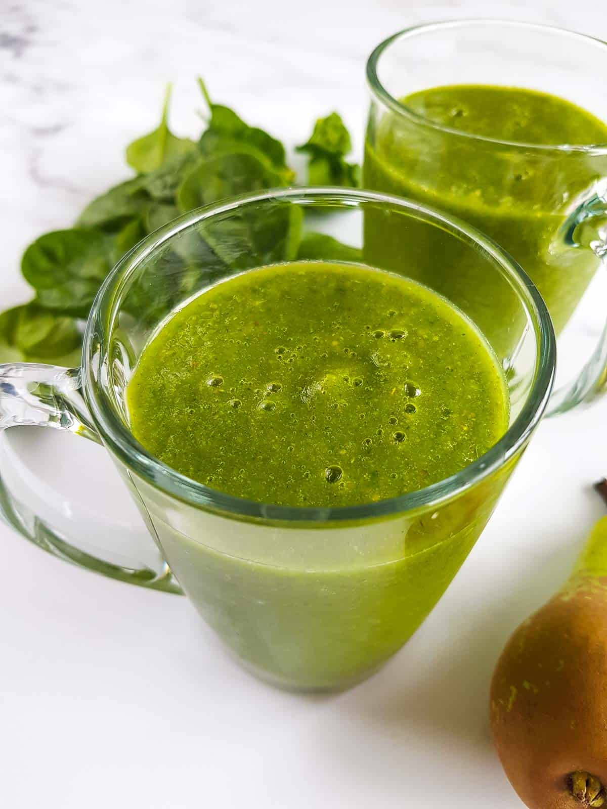 Two cups of spinach and pear smoothie.