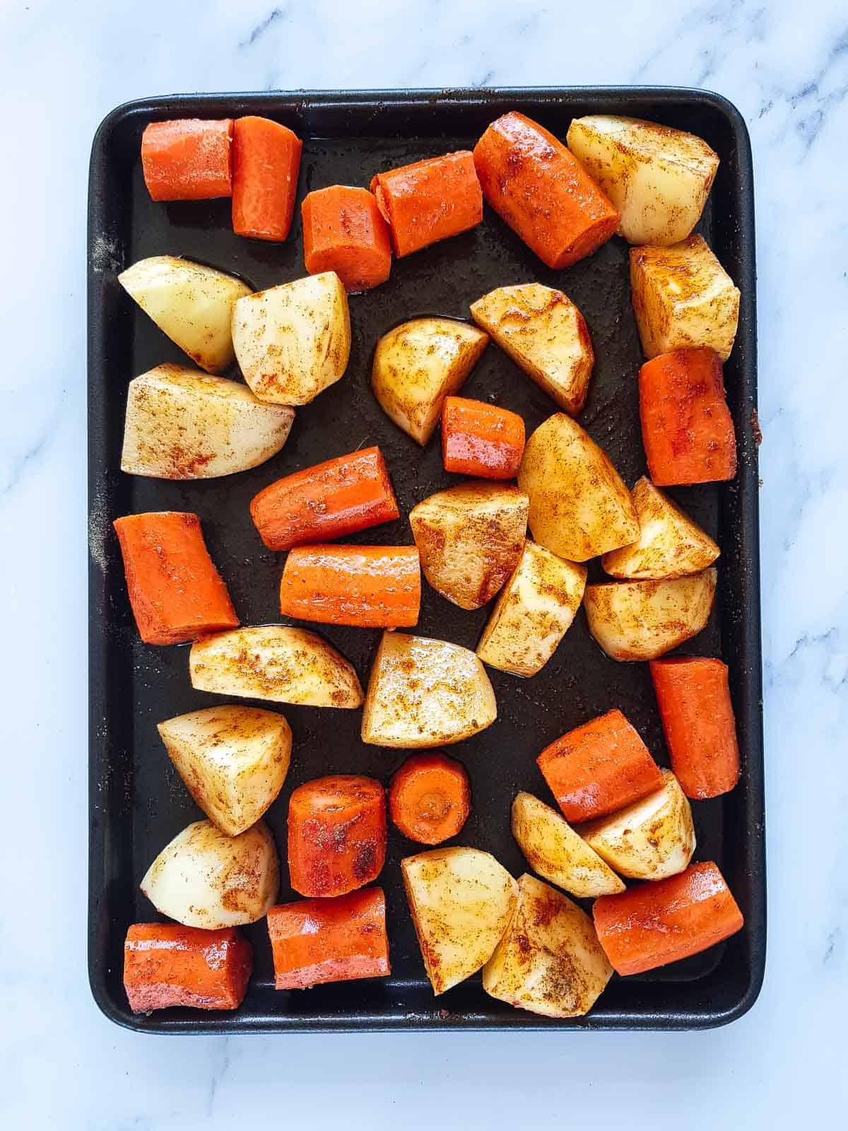 Seasoned carrots and potatoes on a roasting tray.