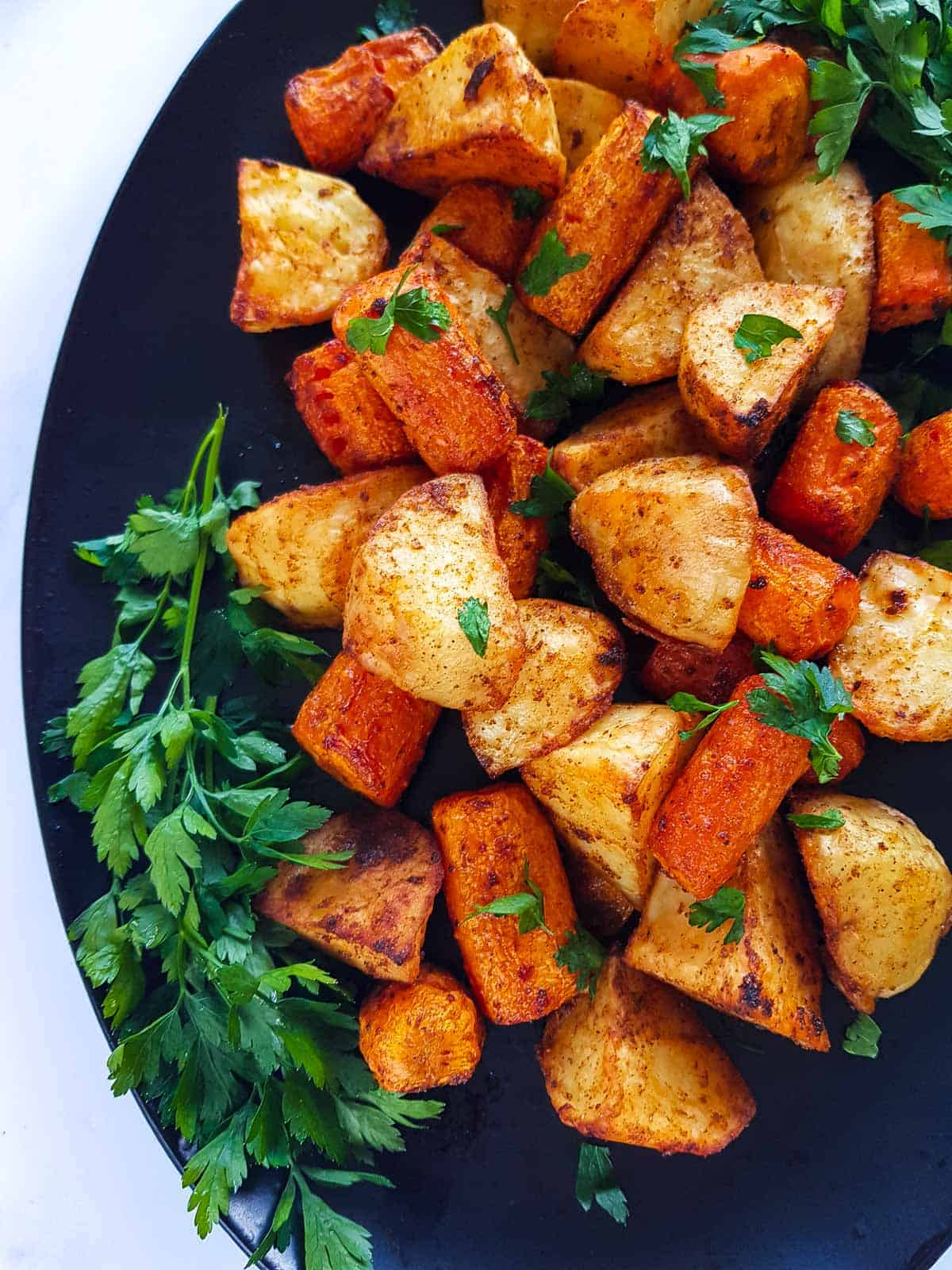 A close up of roasted potatoes and carrots.