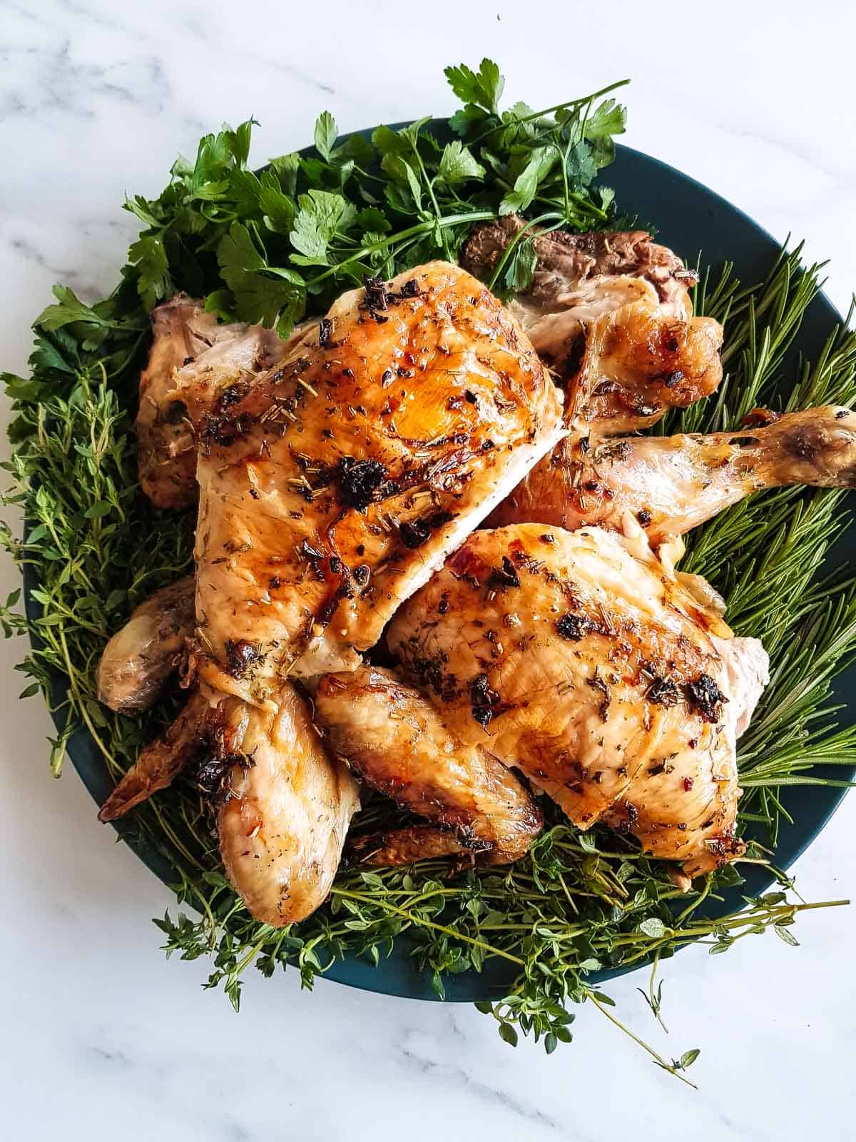 Carved roast chicken on a bed of thyme, rosemary and parsley.