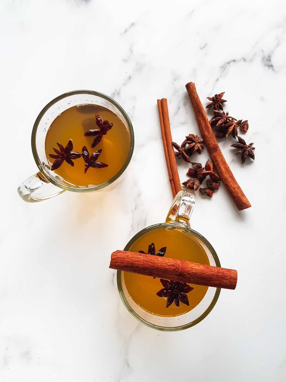 Two cups of star anise tea, with cinnamon sticks and star anise on the side.