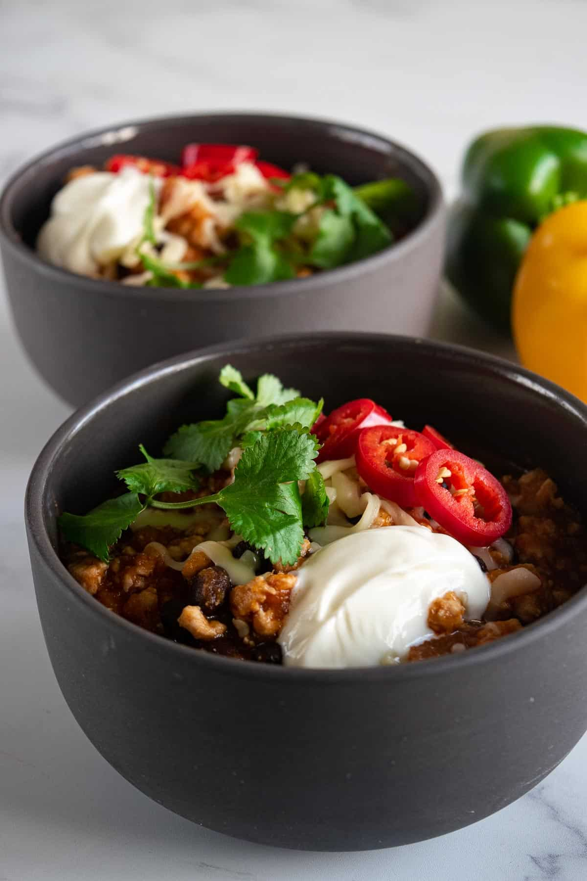 Two bowls of turkey sweet potato chili topped with chili, cilantro and yogurt.