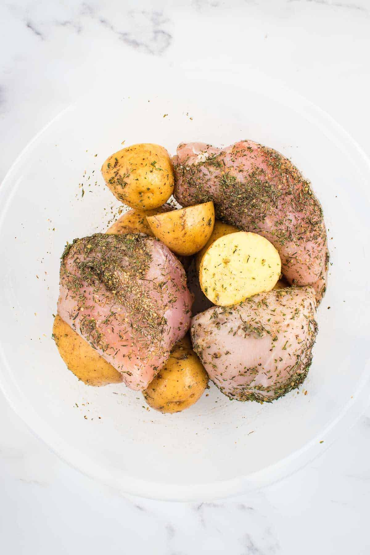 Raw chicken breasts, potatoes and seasoning in a bowl.