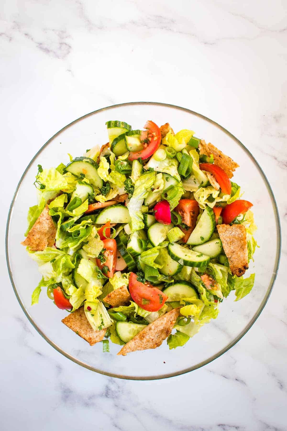 A bowl of Fattoush salad on a marble table.