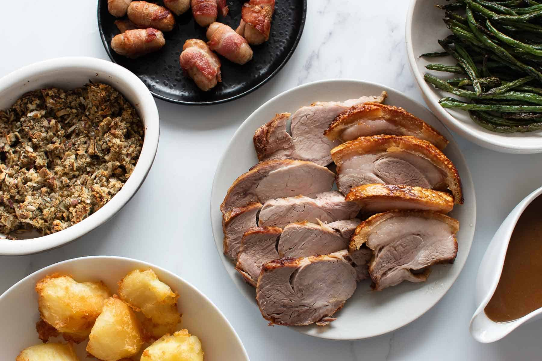 Sliced pork roast on a plate surrounded by side dishes.