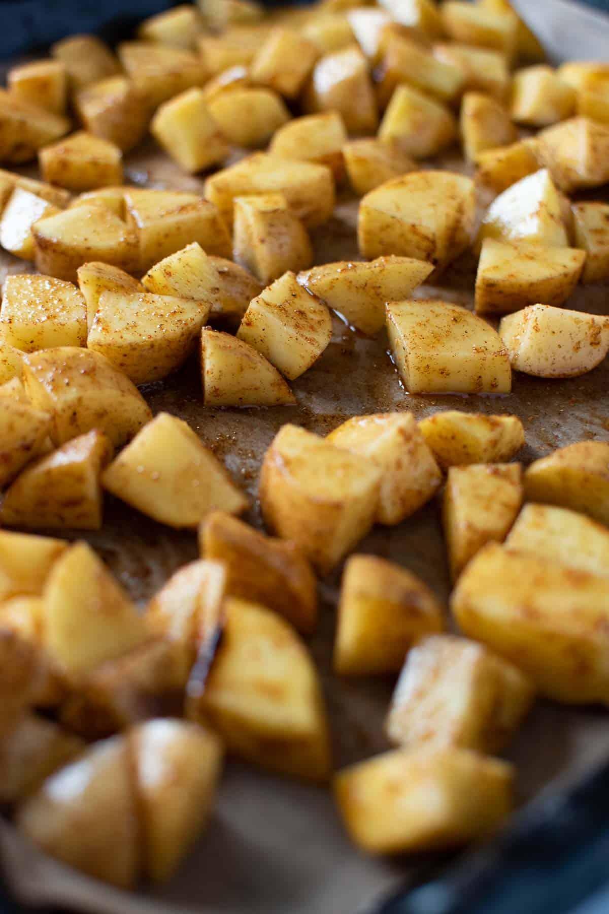 Seasoned diced potatoes on a sheet pan.