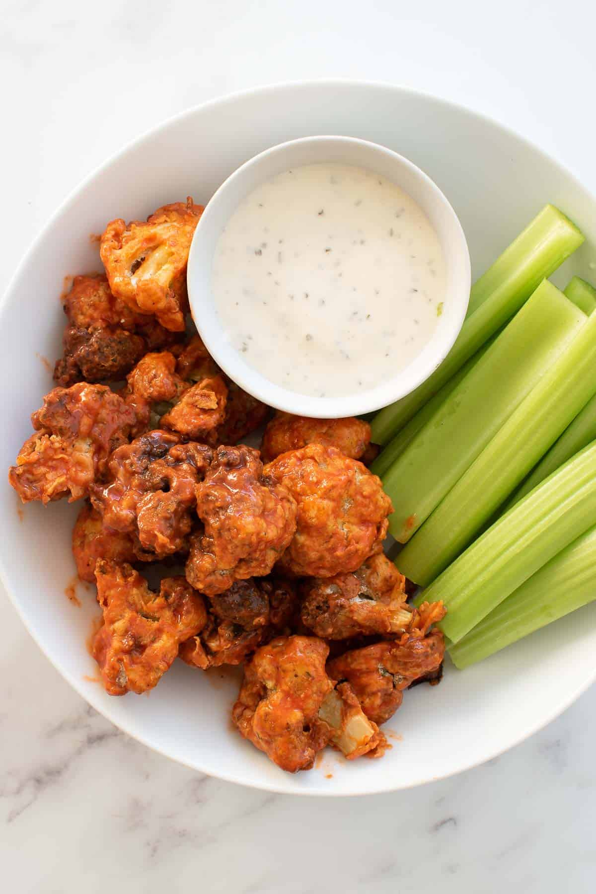 A plate with buffalo cauliflower wings, celery and dip.