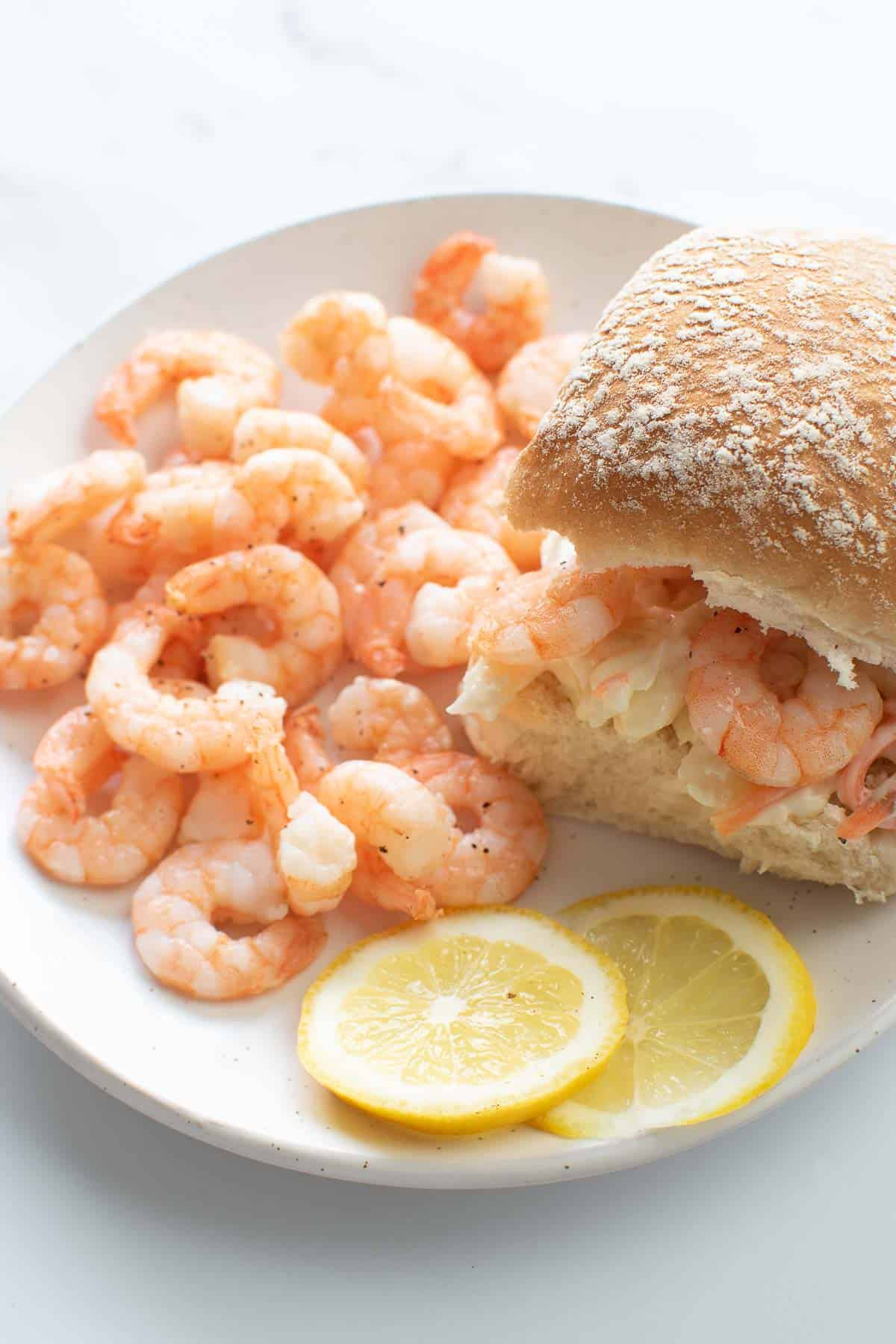 Shrimp sliders with coleslaw and lemon slices.