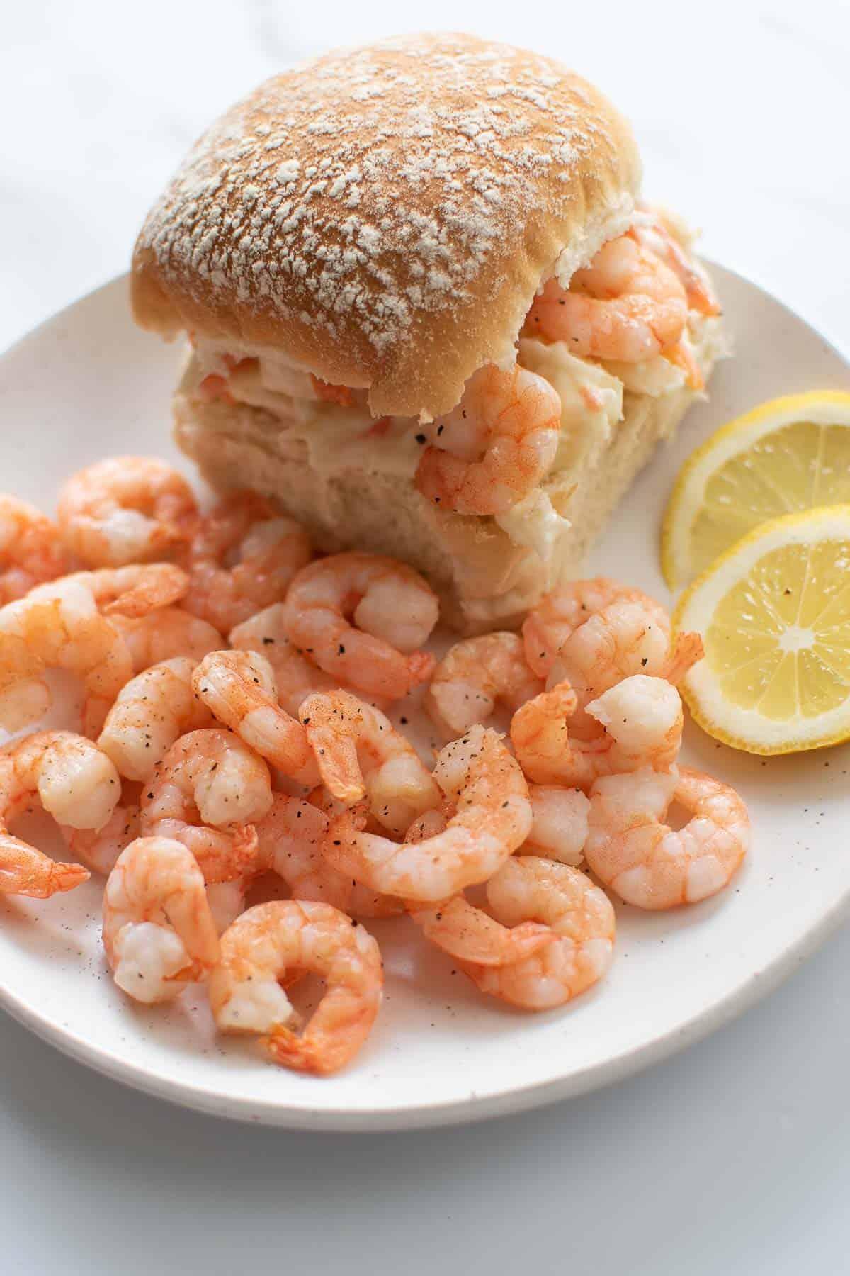 Shrimp on a plate, next to a shrimp and coleslaw slider.