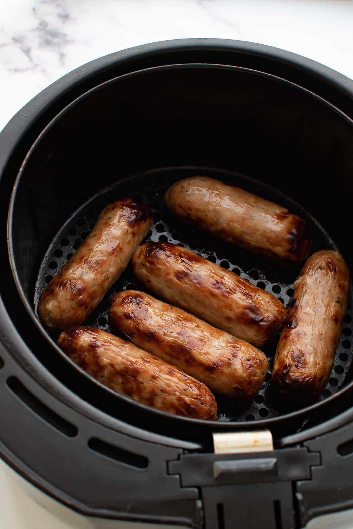Cooked sausages in an air fryer basket.