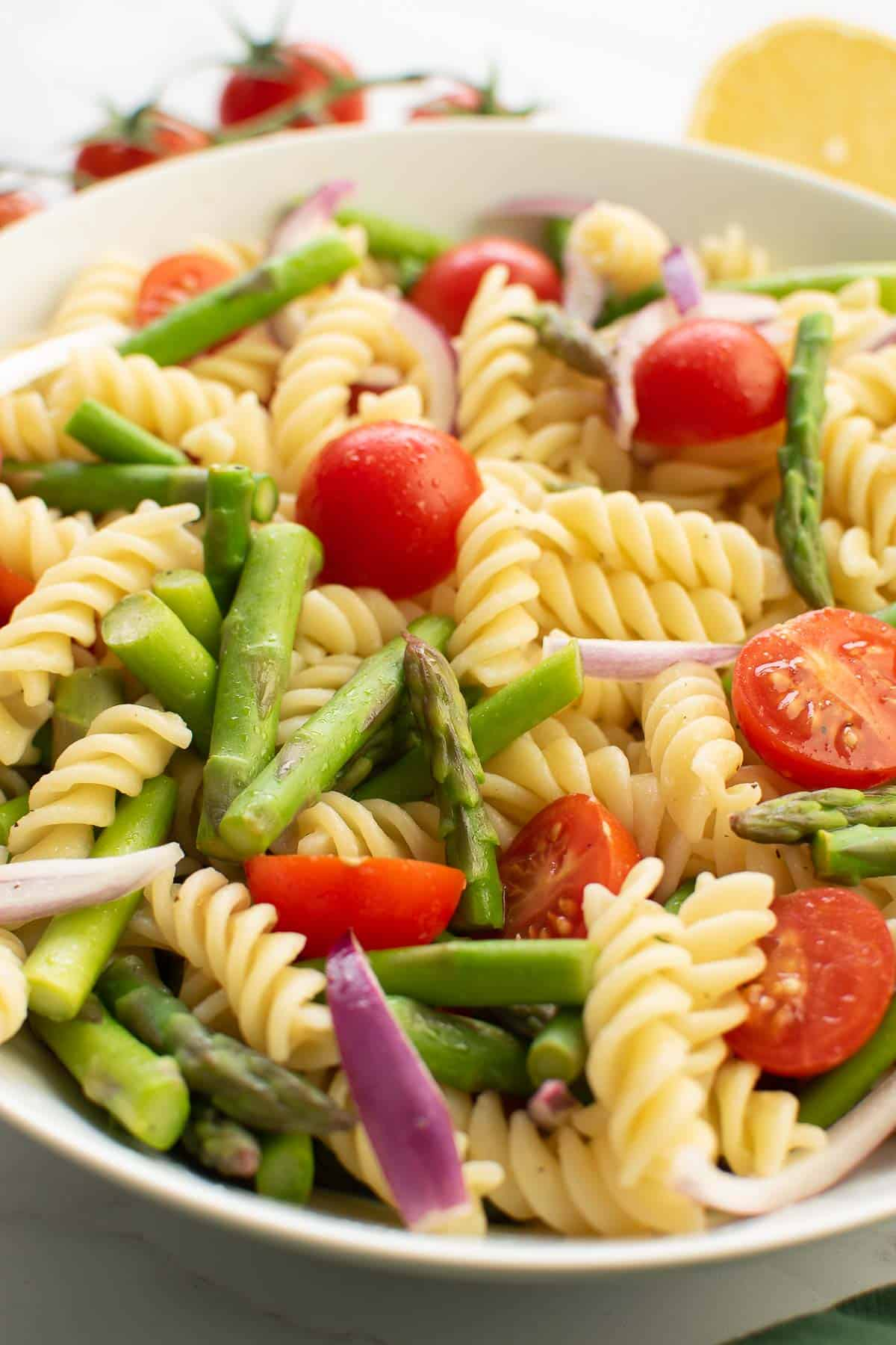Close up of asparagus, pasta and tomatoes in a bowl.