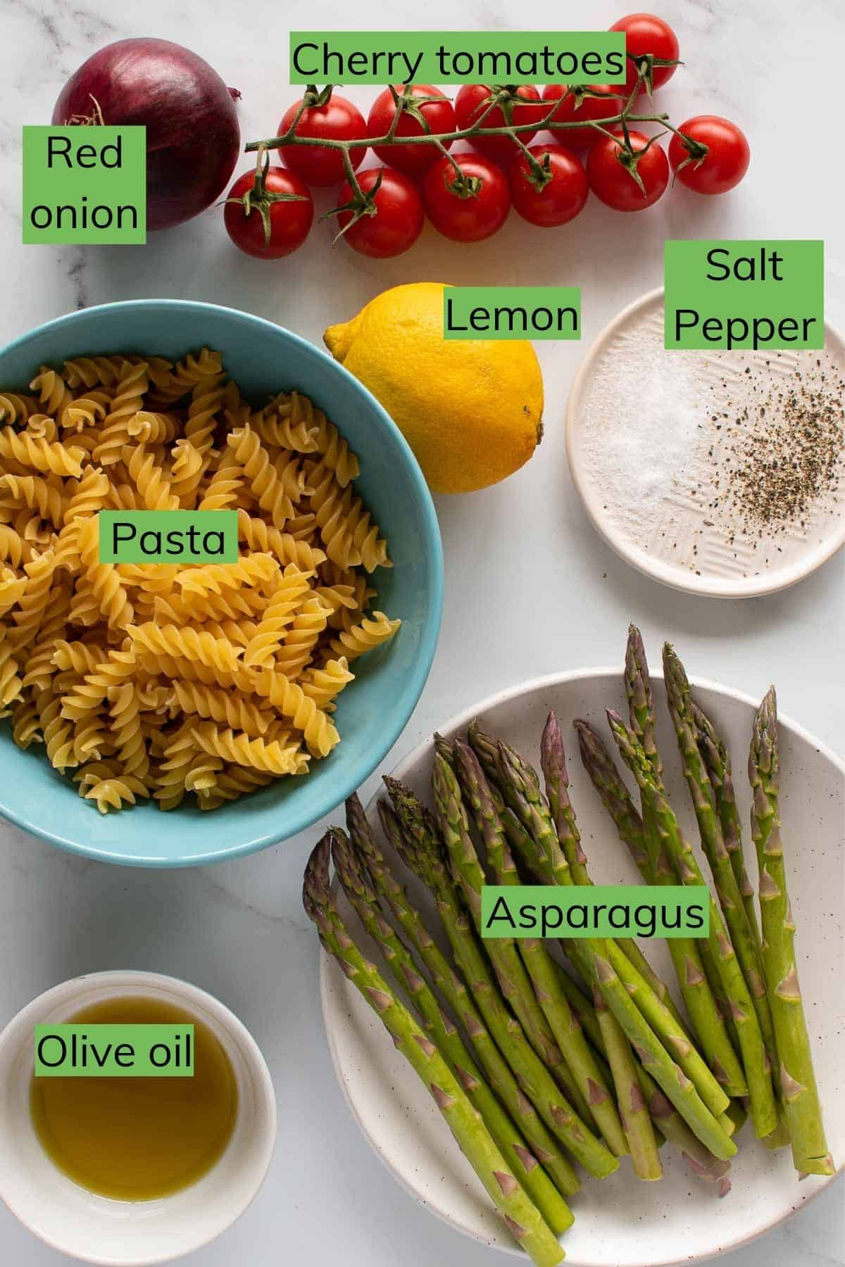 Ingredients required for asparagus pasta salad laid out on a table.