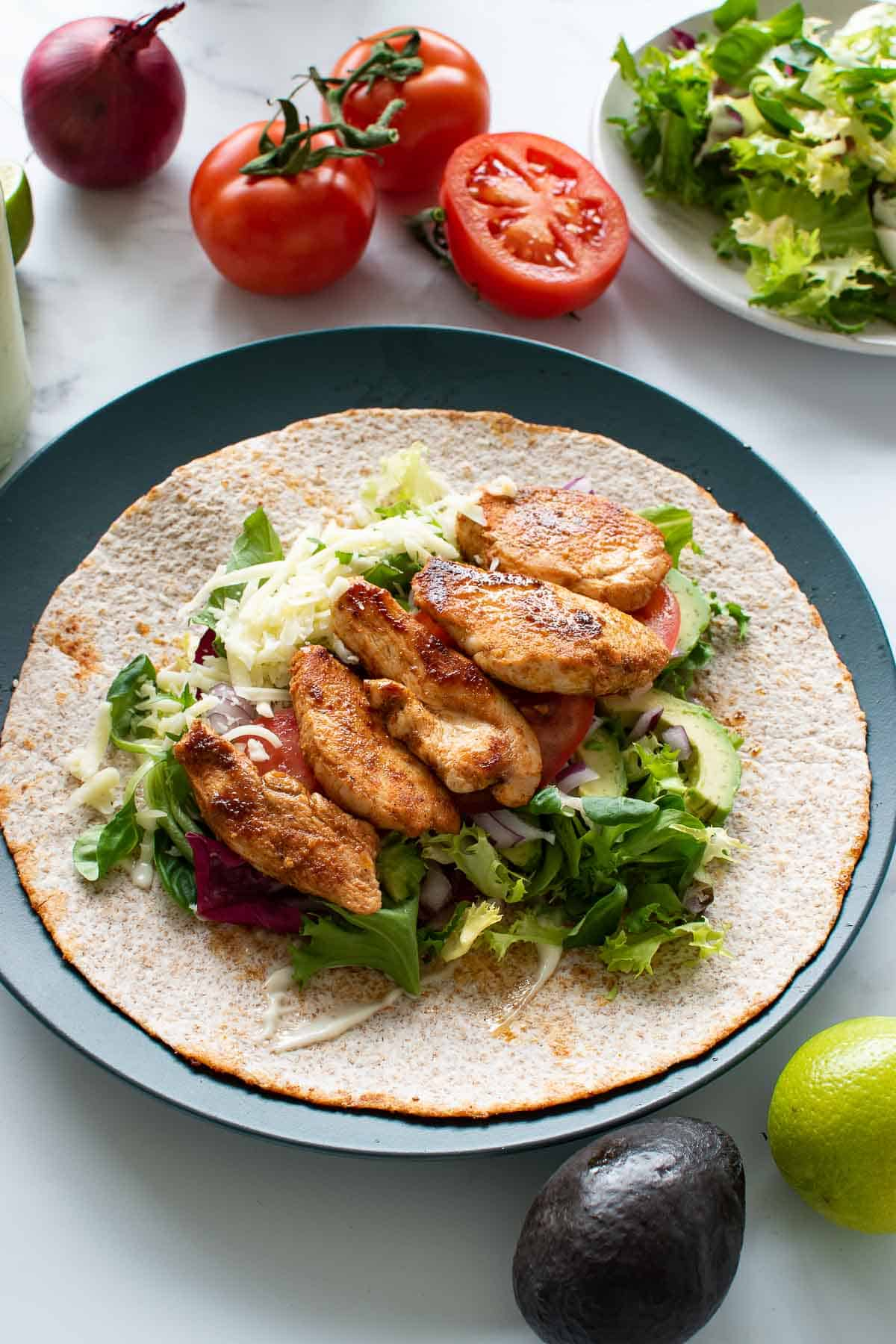A plate with a chicken wrap, with tomatoes and lettuce in the background.