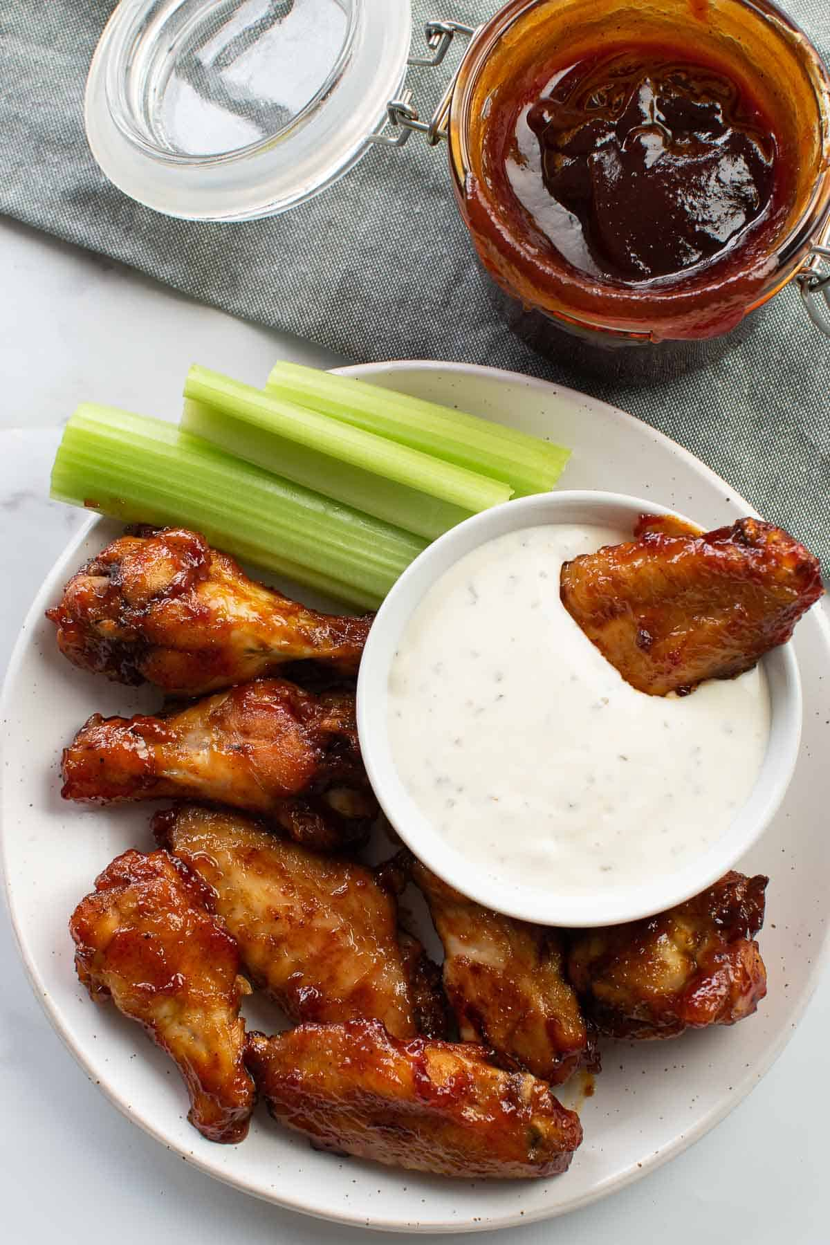 Baked BBQ chicken wings on a plate with a bowl of ranch and celery sticks.