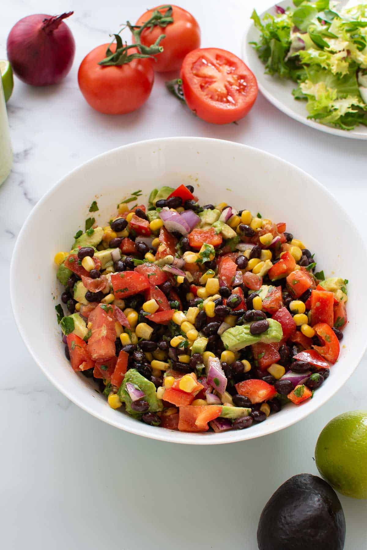 A bowl with black bean corn salad, with vegetables on the side.