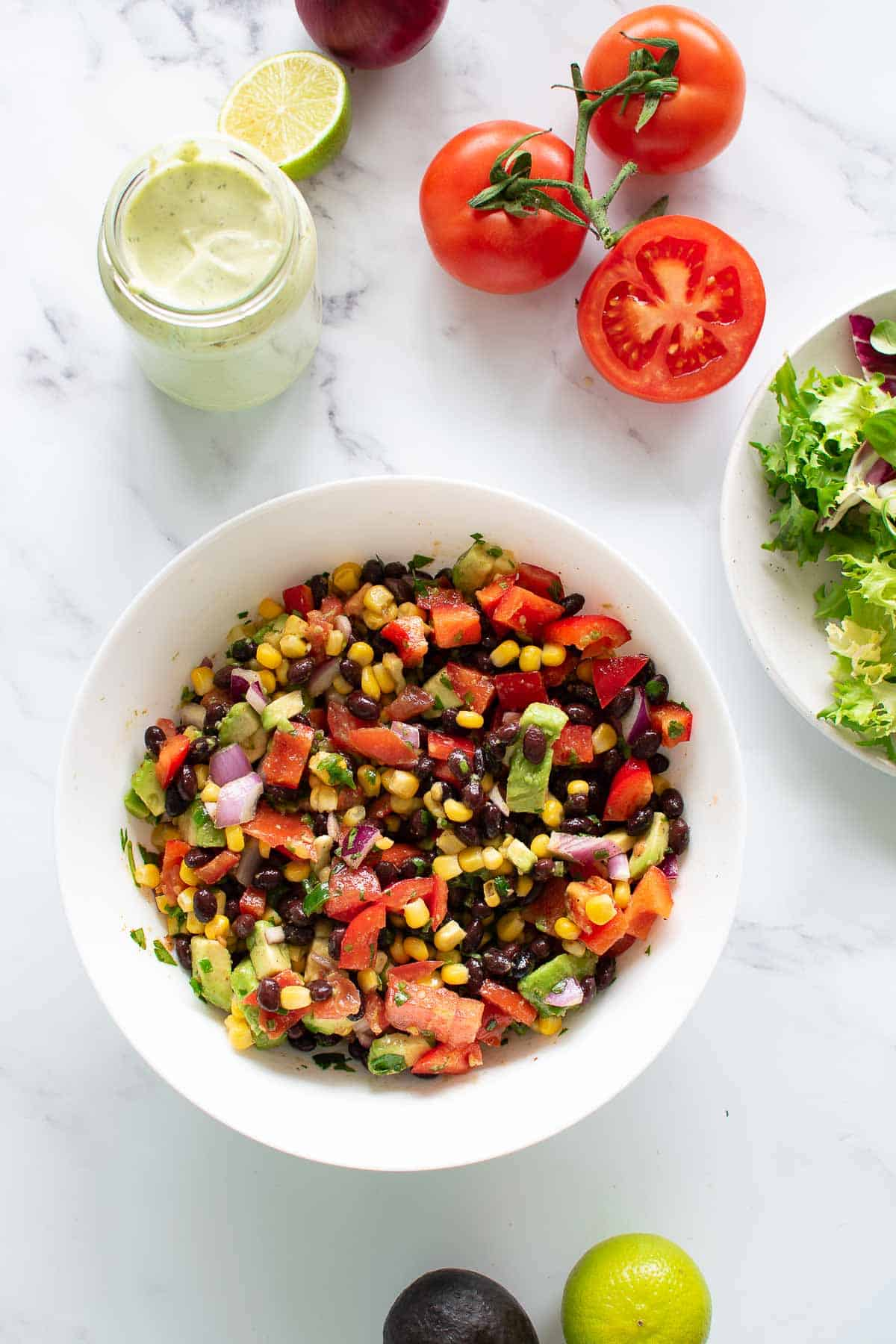 A bowl filled with Tex Mex corn avocado and black bean salad.