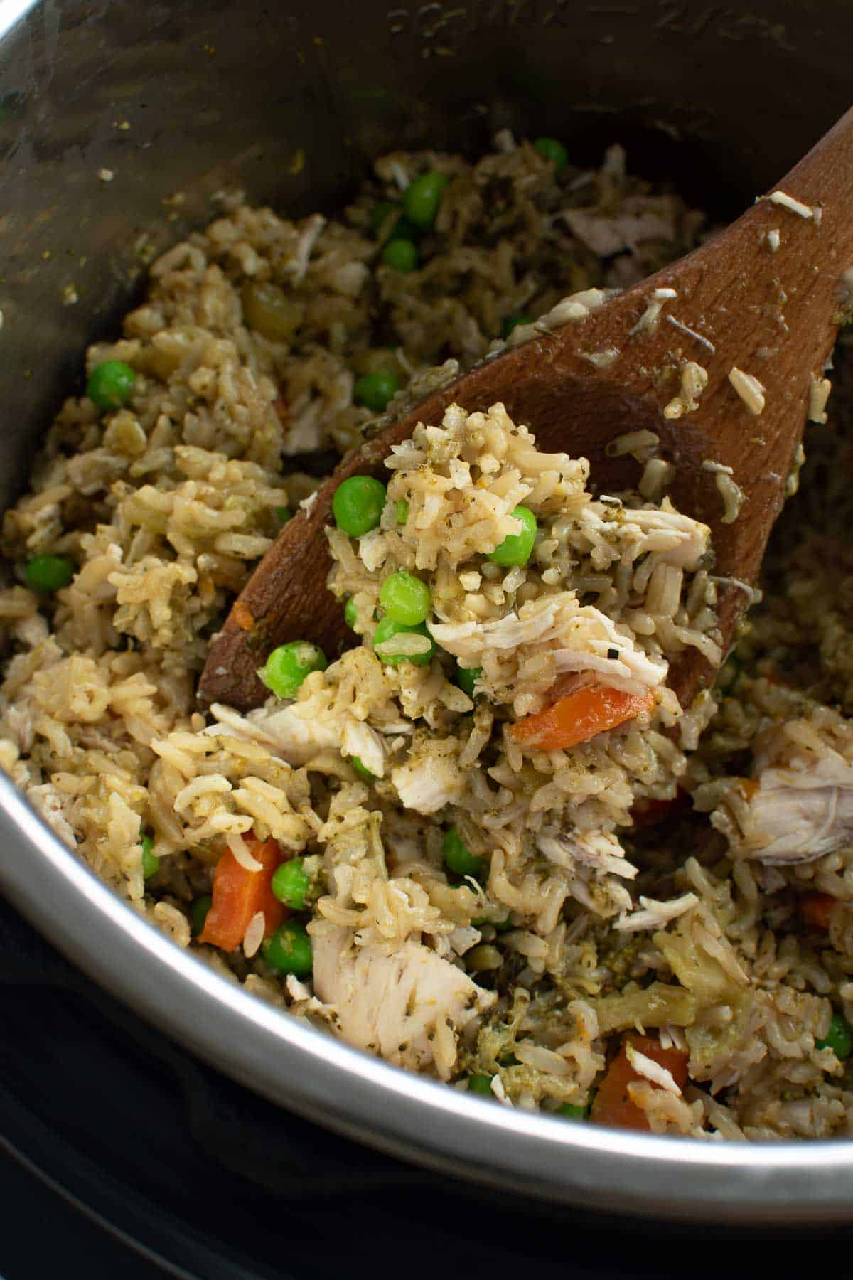 Chicken and rice in instant pot, with a spoon lifting up a serving.