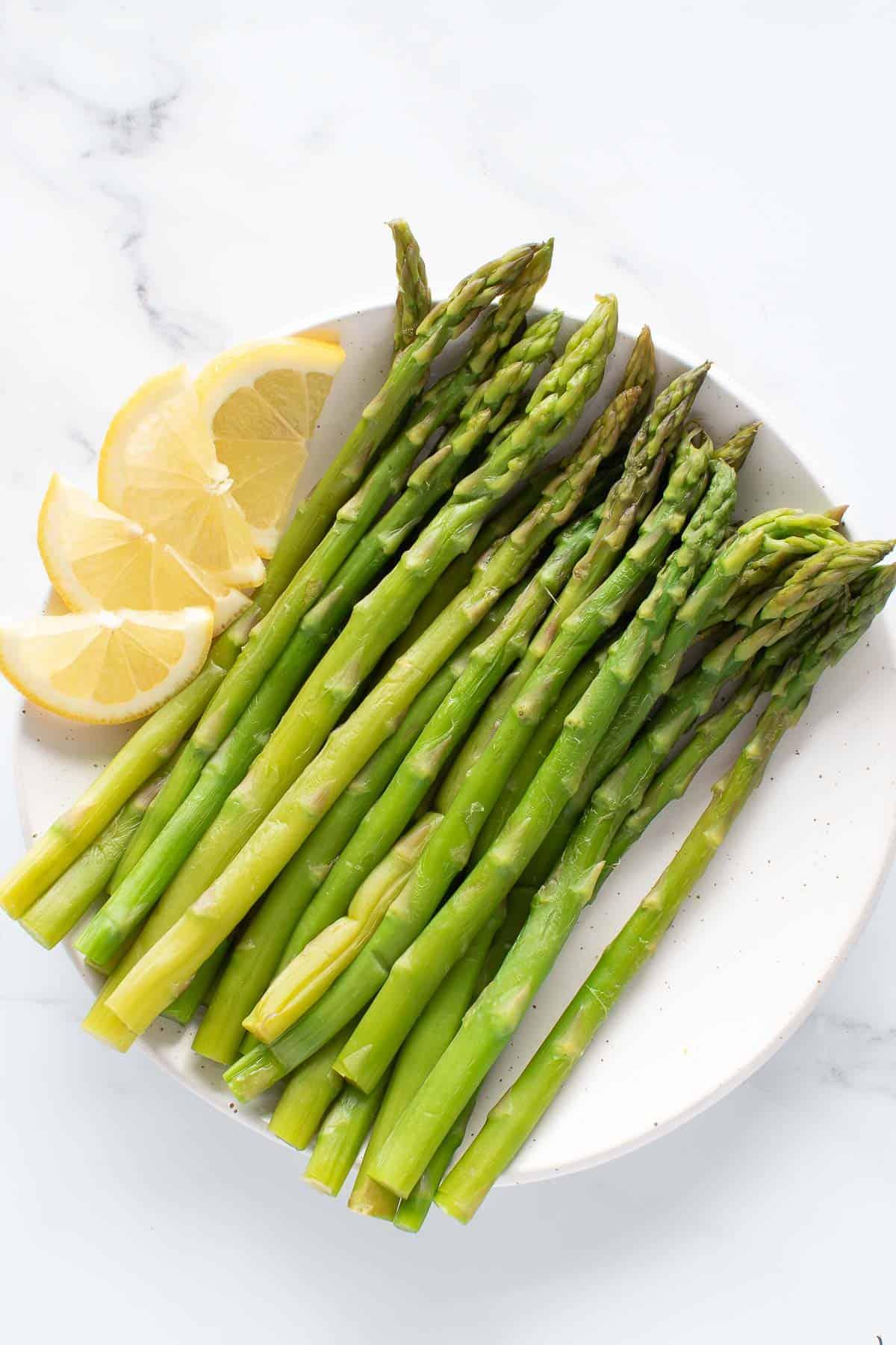 Steamed asparagus with lemon on a plate.