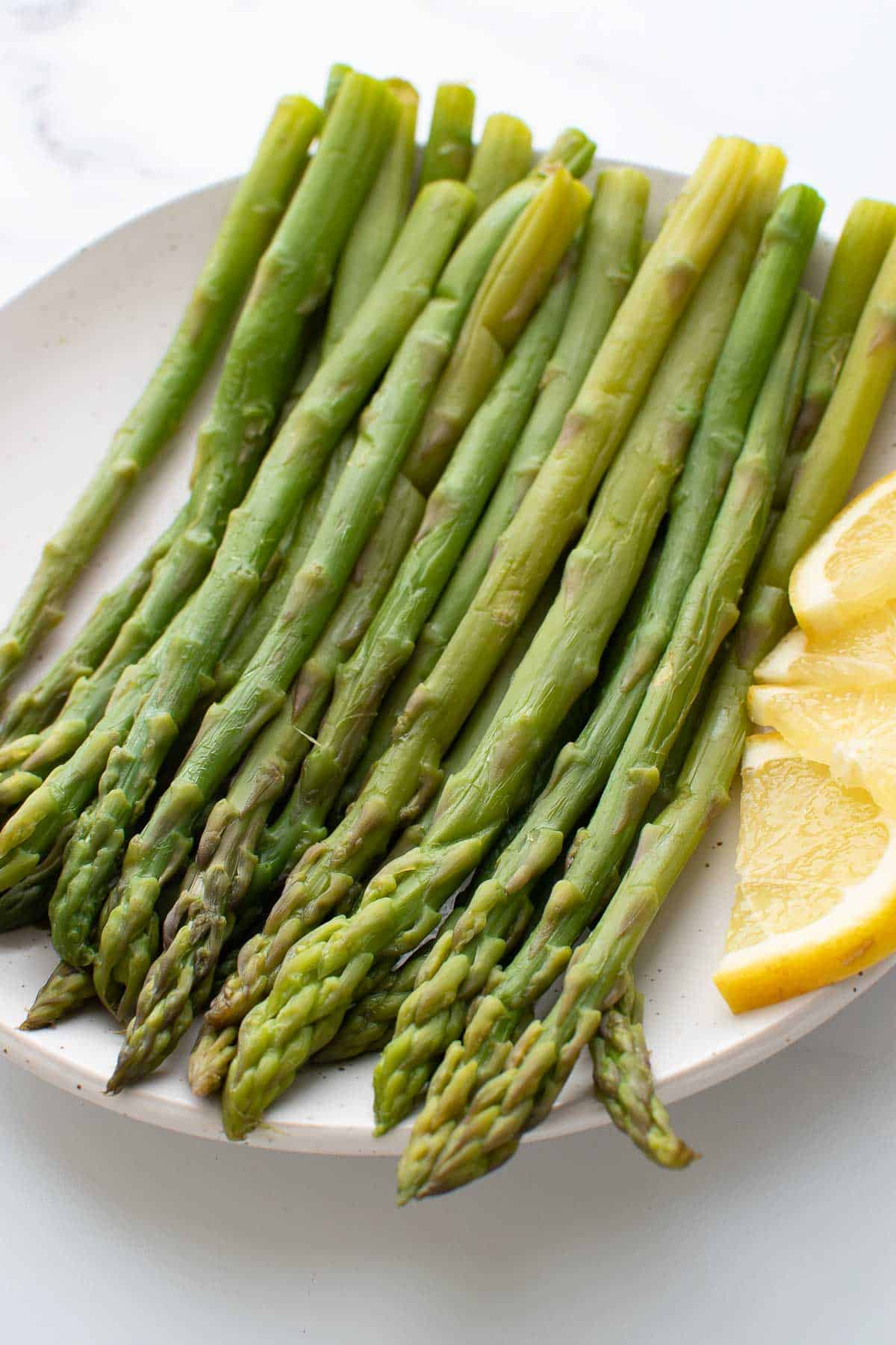 Close up of steamed asparagus with lemon.