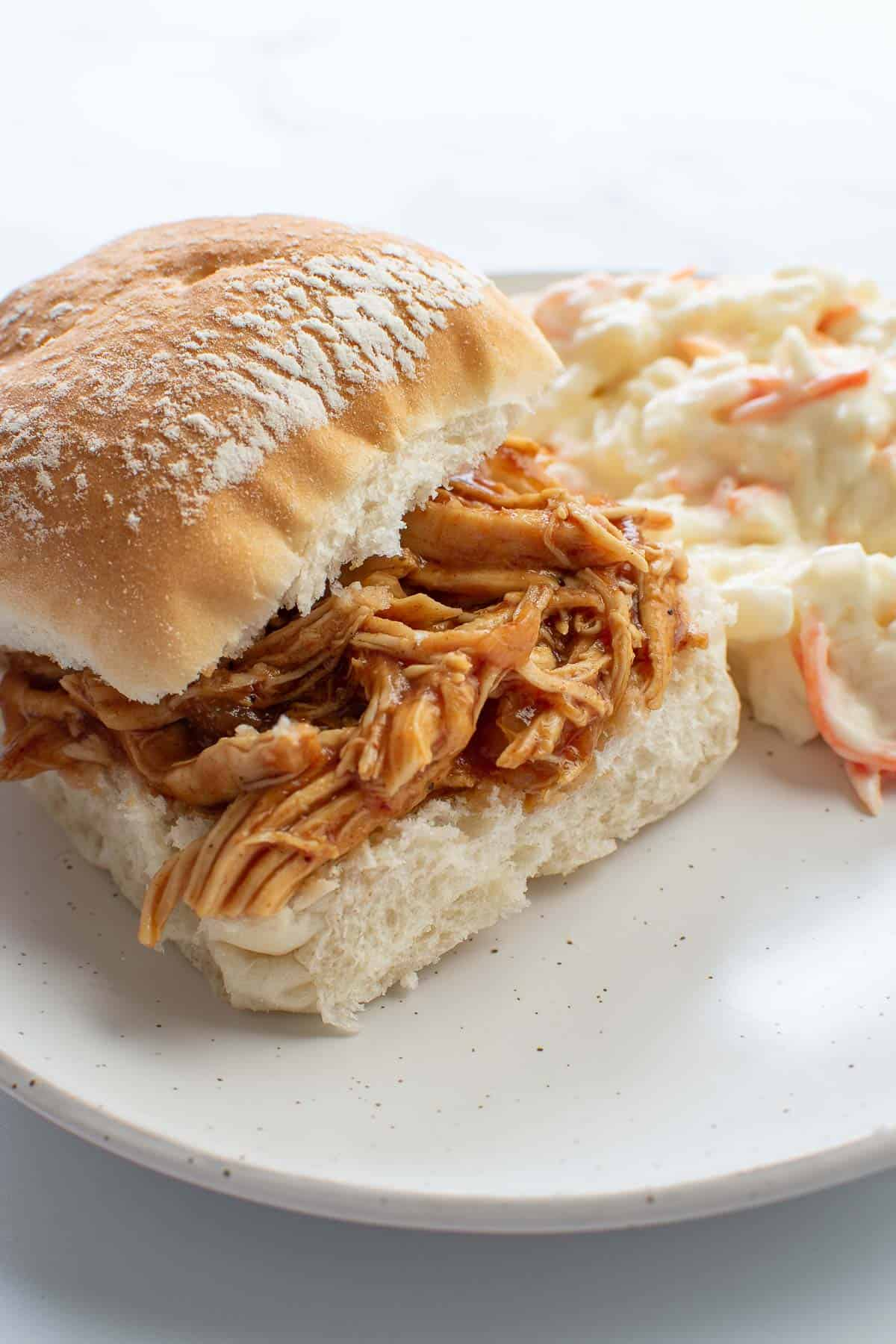 A shredded chicken slider with coleslaw on the side.