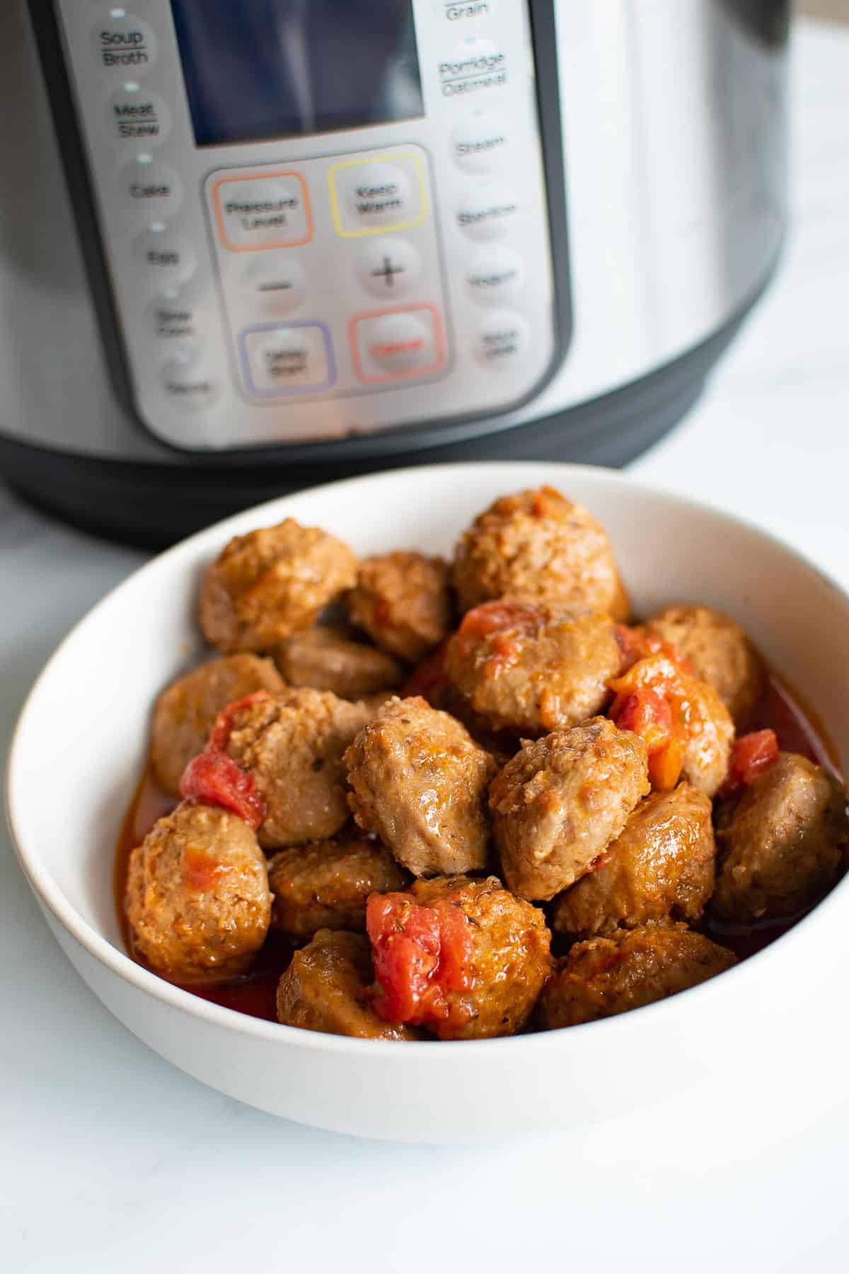 A bowl of meatballs in front of an instant pot.