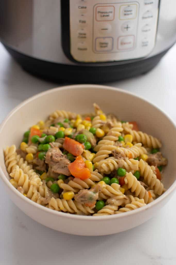 Tuna casserole in a bowl, with an instant pot in the background.