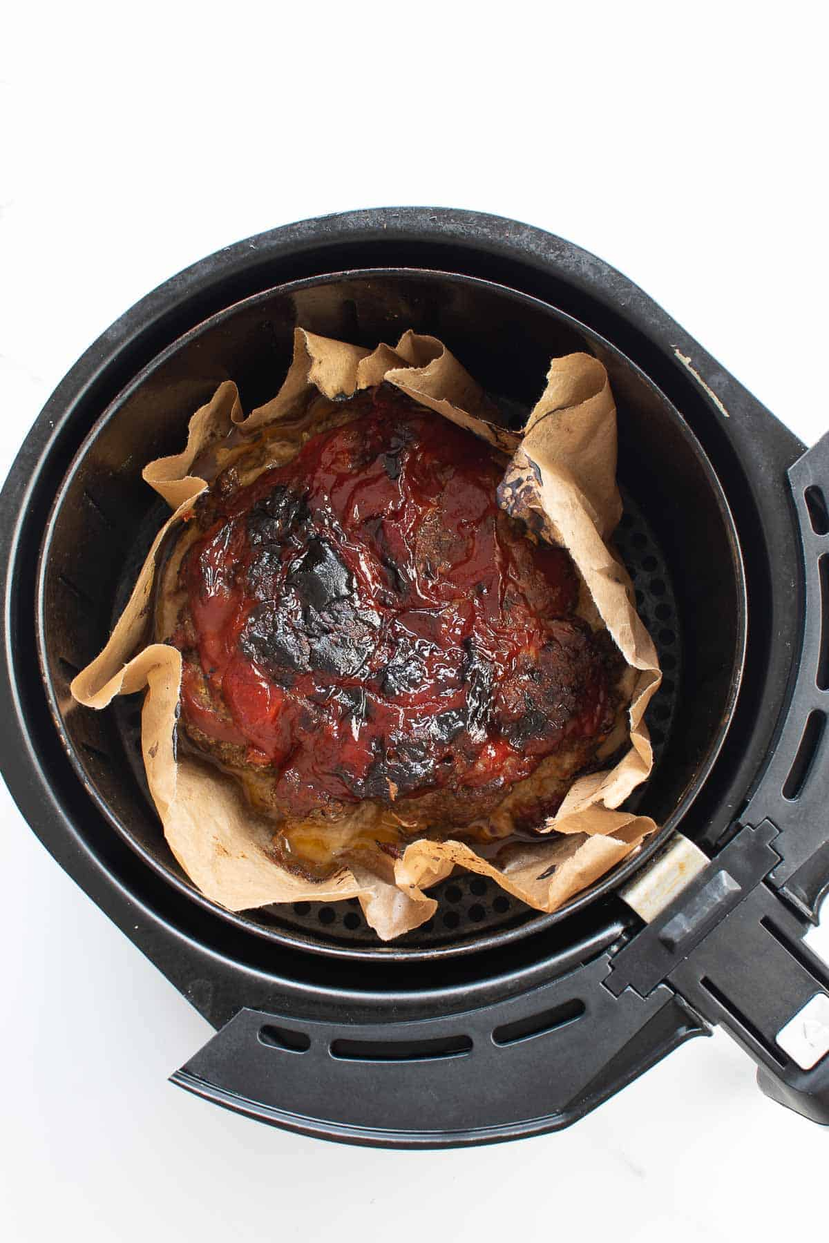 A cooked meatloaf in an air fryer.