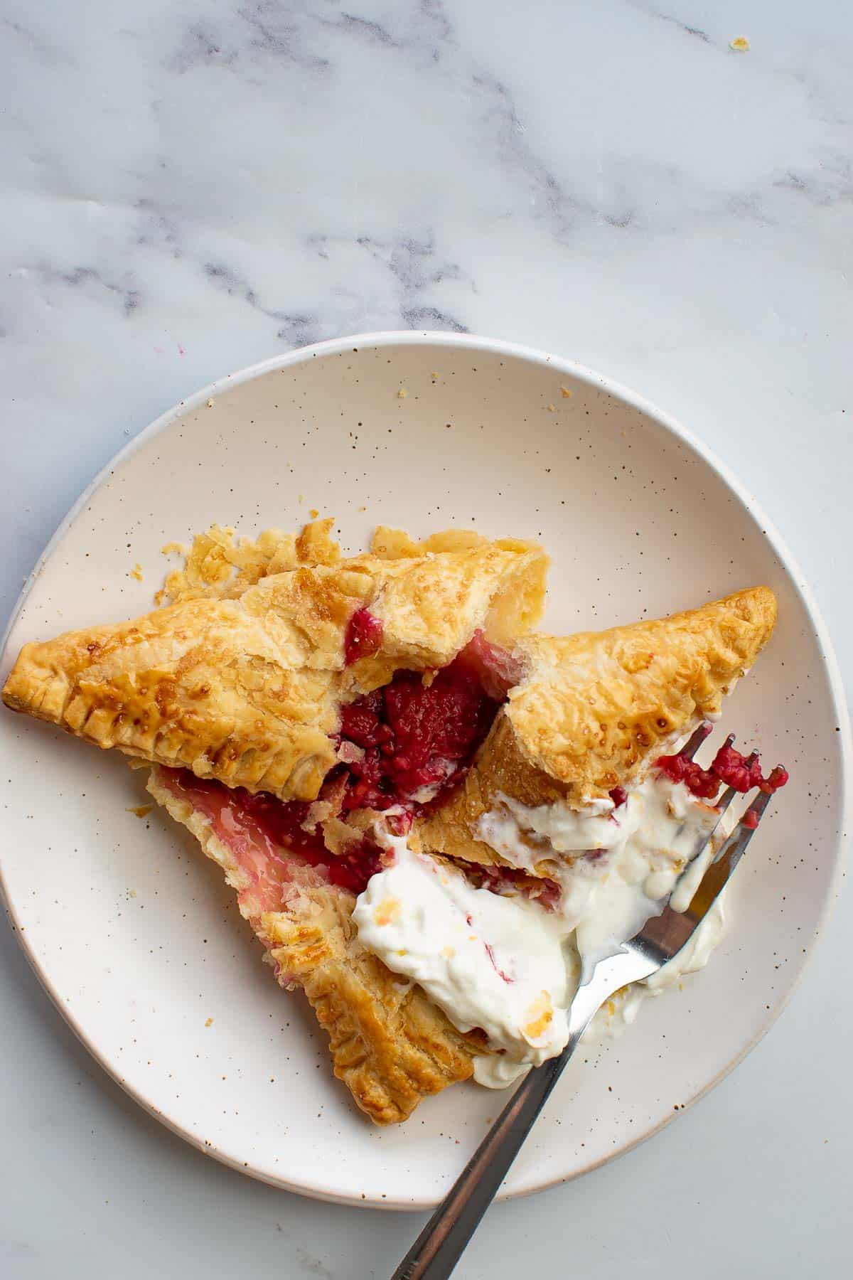 A raspberry pastry with cream that's been opened with a fork.